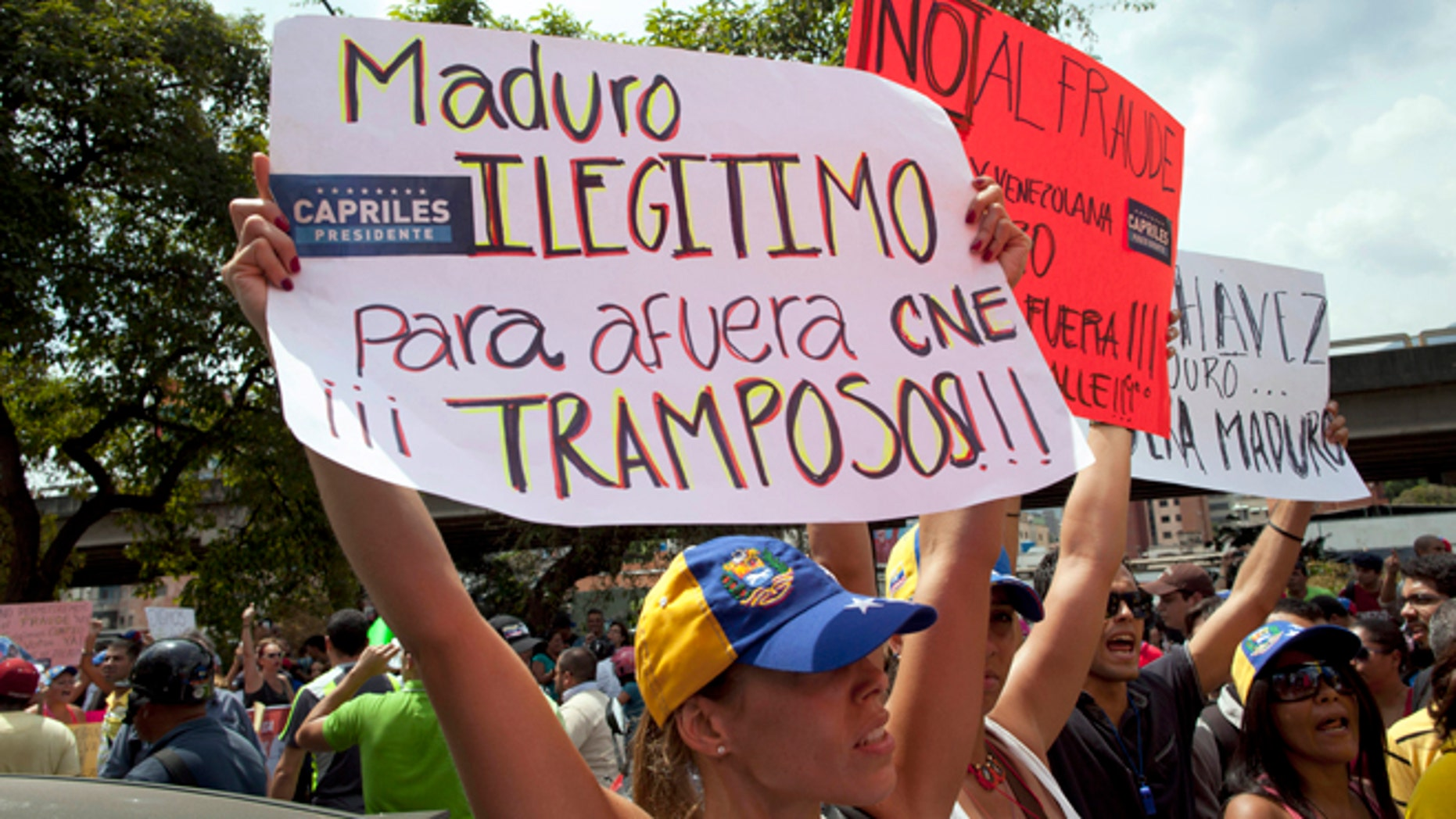 """Opposition supporters protest the official results of the presidential election holding a sign that reads in Spanish """"Maduro, illegitimate, get out CNE."""