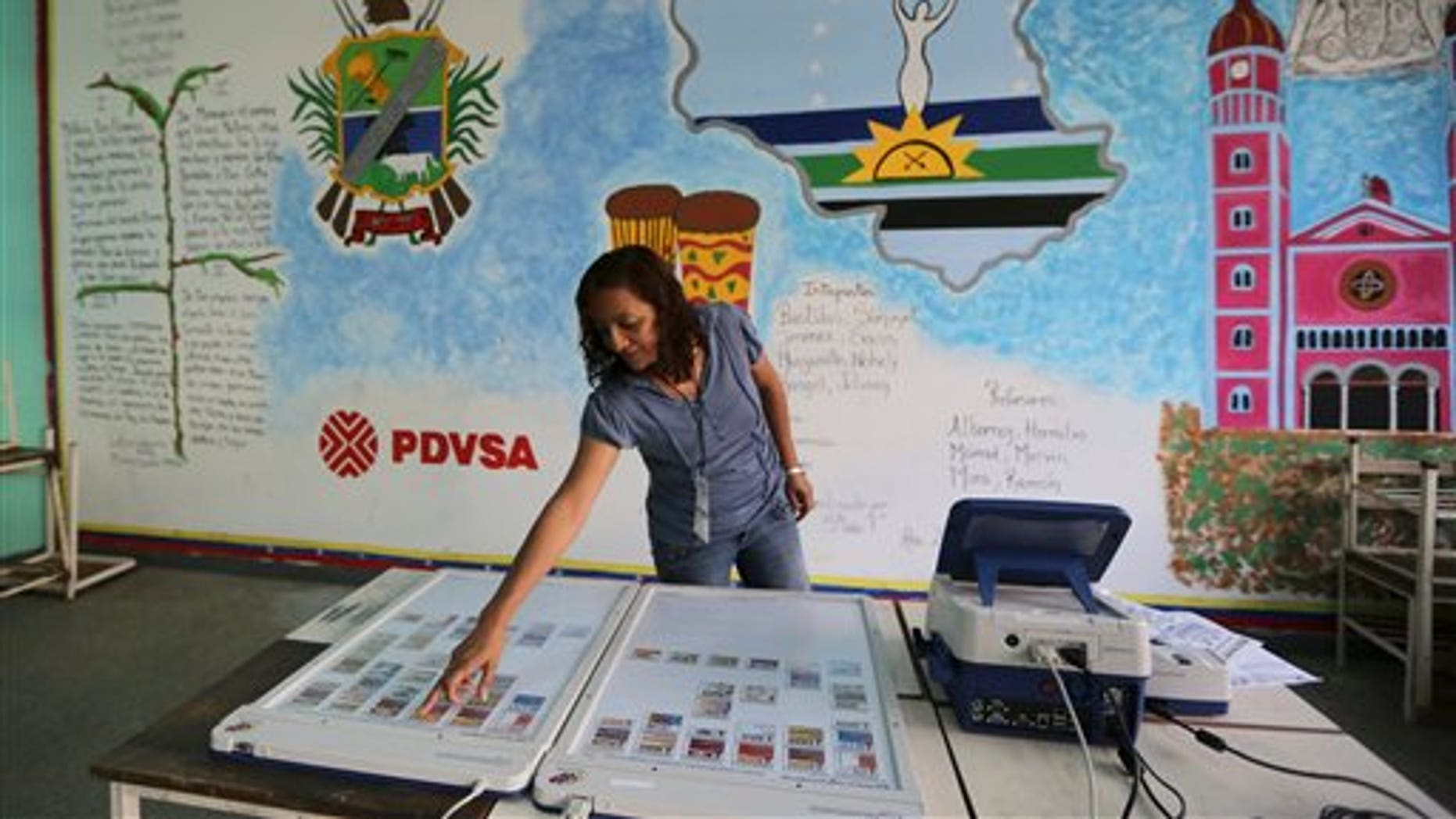 A member of the Venezuelan National Electoral Council tests a voting machine at a polling station in Caracas, Venezuela, Friday, Dec. 6, 2013. Venezuelans will vote in nationwide municipal elections Sunday. (AP Photo/Fernando Llano)