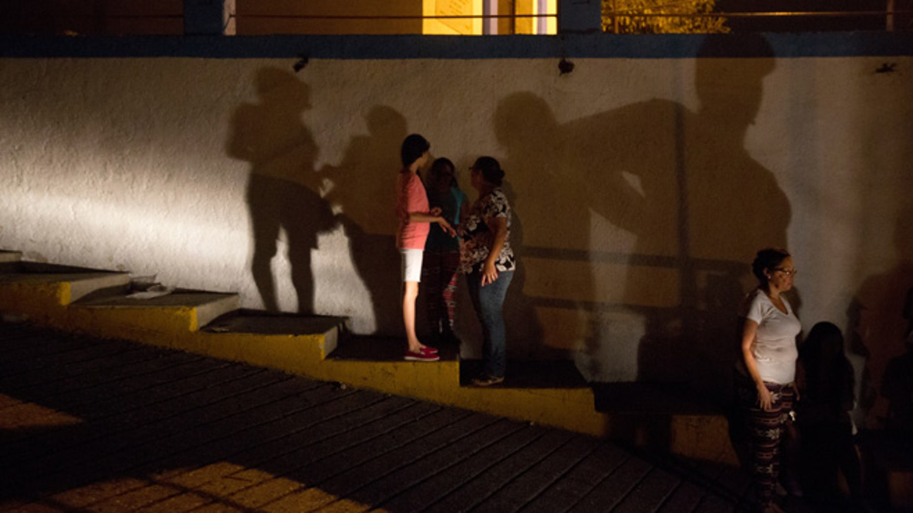 In this Saturday, April 23, 2016 photo, residents make their way to a protest against energy rationing after going through a 24-hour blackout, in the El Calvario neighborhood of El Hatillo, just outside of Caracas, Venezuela. Energy rationing has been added to the hardships faced by Venezuelans overwhelmed by inflation, shortages of food and medicine and rising crime. (AP Photo/Fernando Llano)