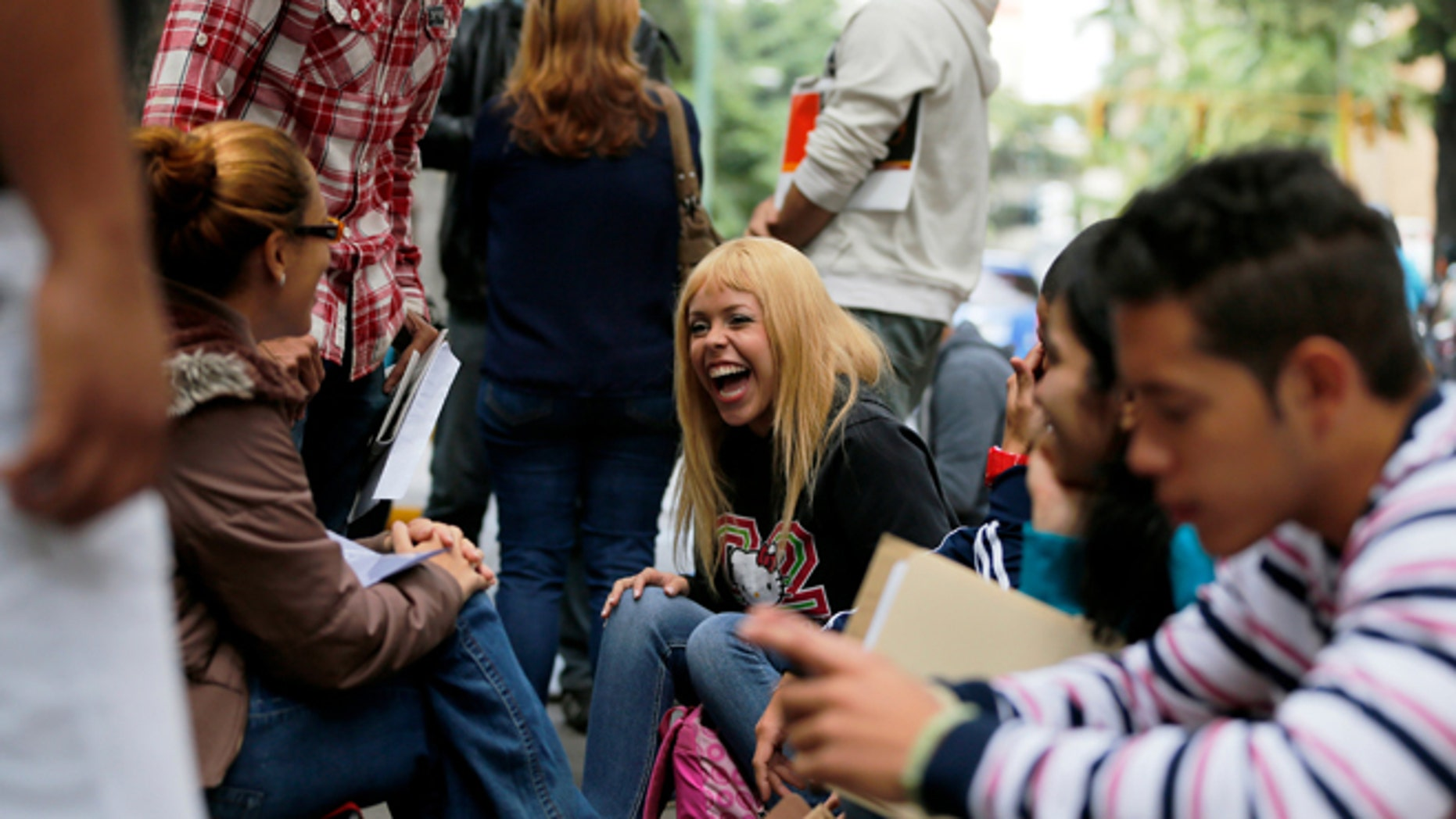 """In this Jan. 28, 2014 photo, Daniela Rodriguez laughs with friends as she waits outside Ireland's consulate in Caracas, Venezuela. Venezuela's best and brightest are abandoning their homeland in droves. """"I'll blindly go anywhere,"""" said Rodriguez, who has been unable to find work as a journalist since graduating college in 2010, so instead works as a sales clerk at a clothing store. (AP Photo/Fernando Llano)"""