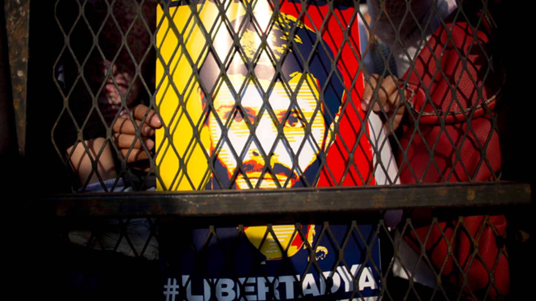 FILE - In this Feb. 20, 2016 file photo, supporters of Venezuela's jailed opposition leader Leopoldo Lopez hold posters of him during a protest demanding the release of Lopez and other jailed opposition leaders, on the second anniversary of his imprisonment, in Caracas, Venezuela. Spain's former Prime Minister Jose Luis Rodriguez Zapatero had a surprise jailhouse meeting with Lopez on June 4, 2016. It's the first time an outside visitor besides Lopez's family or lawyers have met with Lopez in the military prison where he's been held for over two years.  (AP Photo/Ariana Cubillos, File)