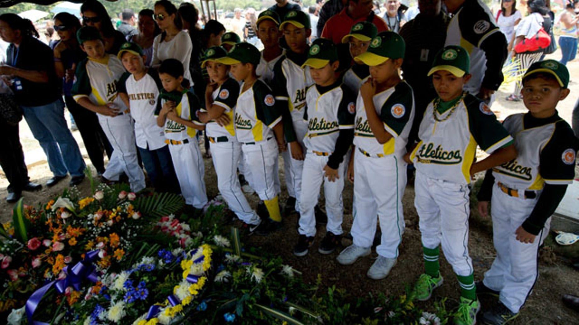 """March 14, 2014: Boys that play in a minor league baseball team """"Atleticos de Crimon"""" mourn their coach, Guillermo Sanchez after his funeral grave in  in Valencia, Venezuela. The people of the poor district of La Isabelica were made to pay for taking to the streets in anti-government protests. More than a dozen masked men on motorcycles roared through, shooting up a barricade and killing a university student and a 42-year-old man painting his house. (AP Photo/Fernando Llano)"""