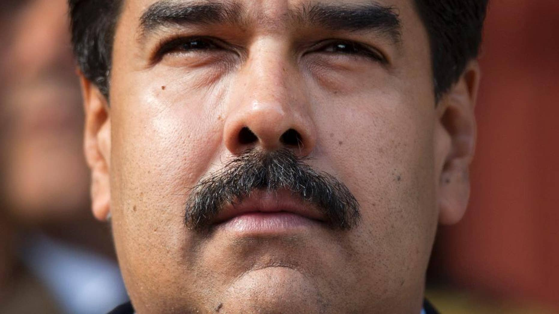 FILE - I this March 17, 2015, file photo, Venezuela's President Nicolas Maduro listens to the playing of national hymns as he welcomes regional leaders to Miraflores presidential palace for an emergency ALBA meeting in Caracas, Venezuela. On Thursday, Oct. 5, 2015, Maduro repeated a promise to shave off his trademark moustache if his government doesn't meet a year-end goal of handing over its 1 millionth public housing unit to a family. (AP Photo/Ariana Cubillos, File)