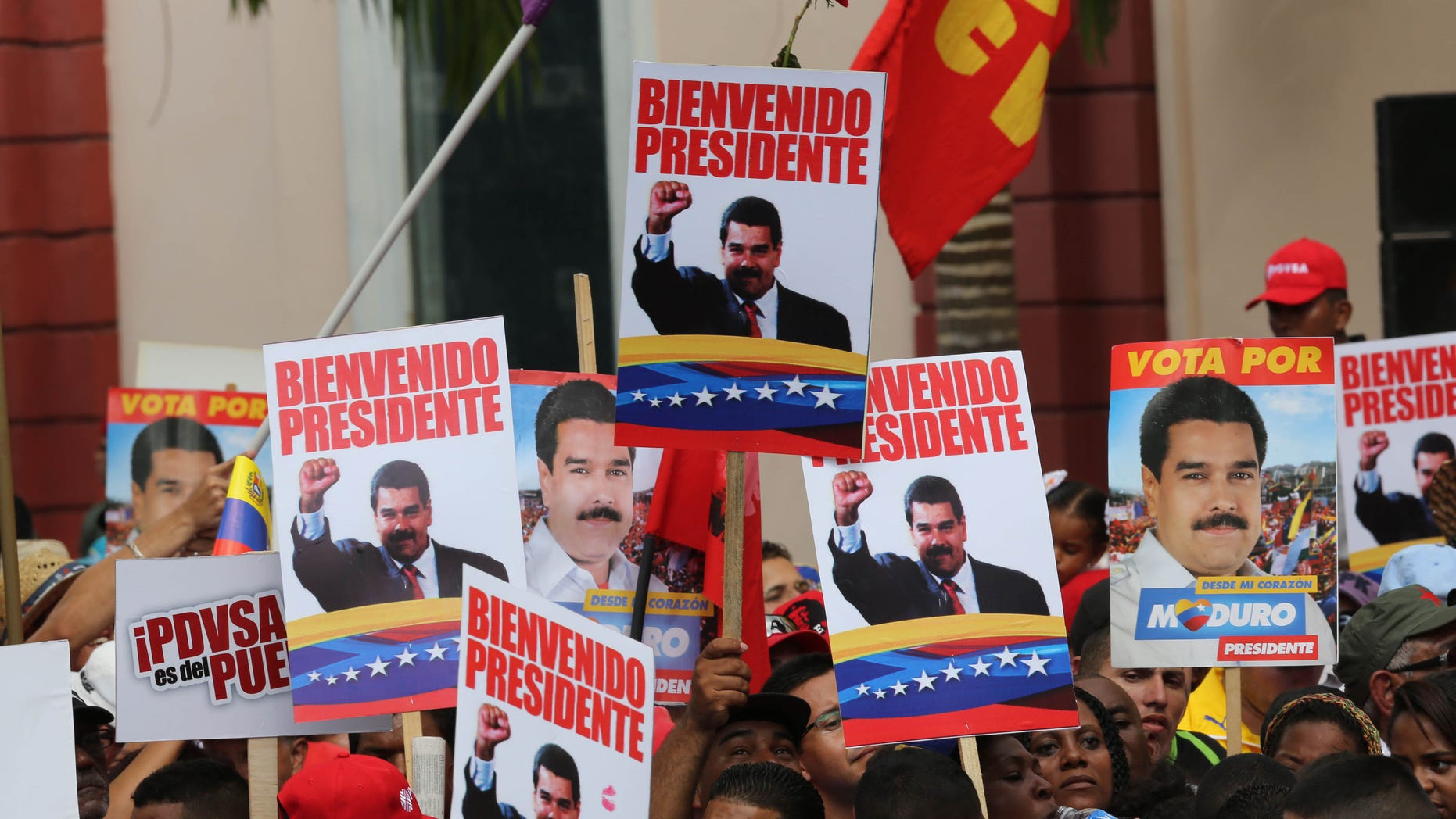 """Supporters hold placards with images of Venezuela's President Nicolas Maduro and a message that reads in Spanish; """"Welcome president,""""at the Miraflores Palace in Caracas, Venezuela, Saturday, Jan. 17, 2015, during a ceremony welcoming the leader back home. Maduro has been away visiting seven nations to seek loans and make a plea for lower oil production. The price of oil has crashed in recent months, driving Venezuelaâs oil-based economy to the brink. (AP Photo/Ariana Cubillos)"""