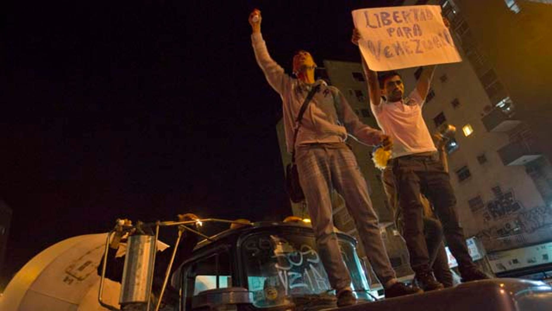 Feb. 19, 2015: Protesters in Caracas, Venezuela stand on the hood of a Mack truck, one holding a sign that reads in Spanish 'Freedom for Venezuela' during a protest sparked by the violent arrest of Caracas Mayor Antonio Ledezma. (AP Photo/Alejandro Cegarra)