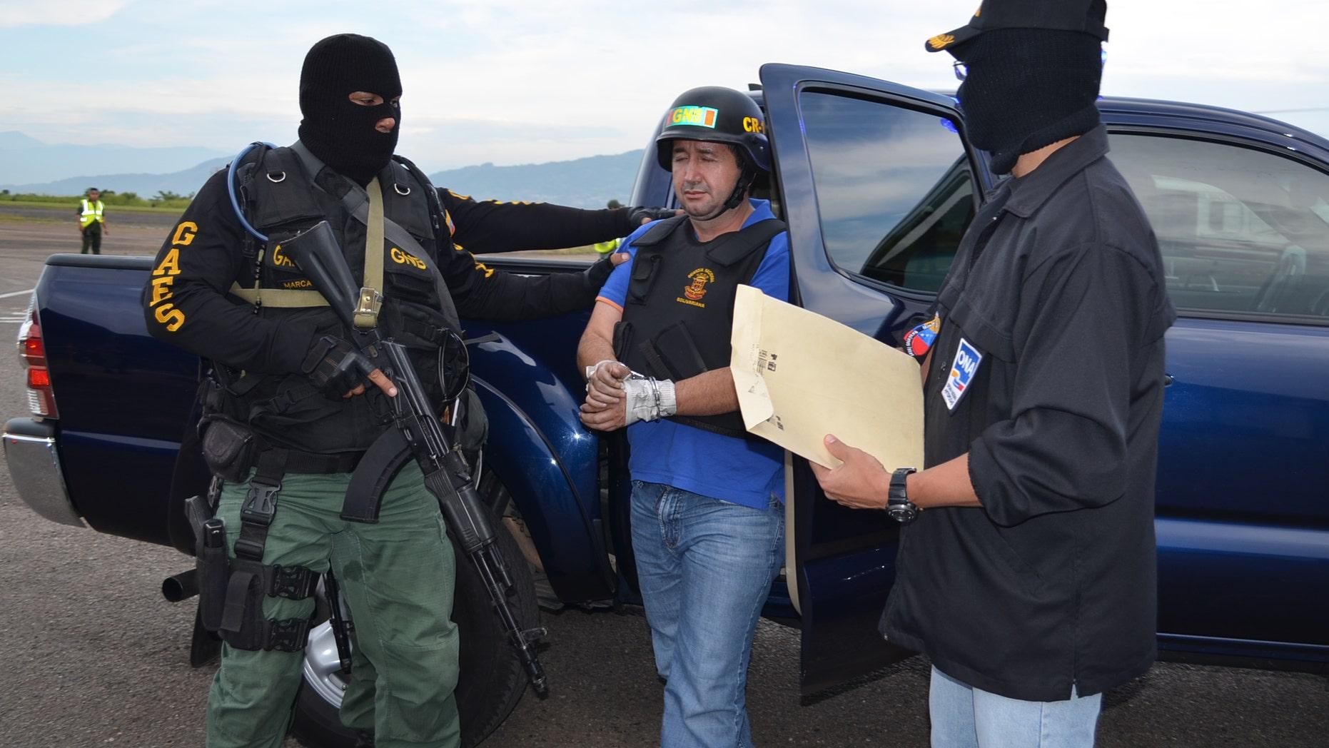 Sept. 19, 2012: Venezuela's judicial police officers escort alleged Colombian drug trafficker Daniel Barrera, center, at the Regional Command No. 1 National Guard base in San Cristobal, Tachira state, Venezuela.