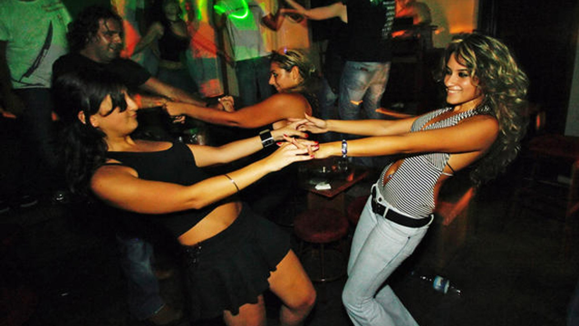 Lebanese women dance in the BOA bar at Monot Street in the Christian heartland of Ashrafieh, an area of Beirut, Lebanon, late Saturday, Aug. 19, 2006. On the sixth day of the UN-brokered cease-fire the Lebanese capital was returning to normal as bars, nightclubs, and restaurants came back to life after 34-day-long fighting between the Israel and Hezbollah guerrillas. (AP Photo/Kevork Djansezian)
