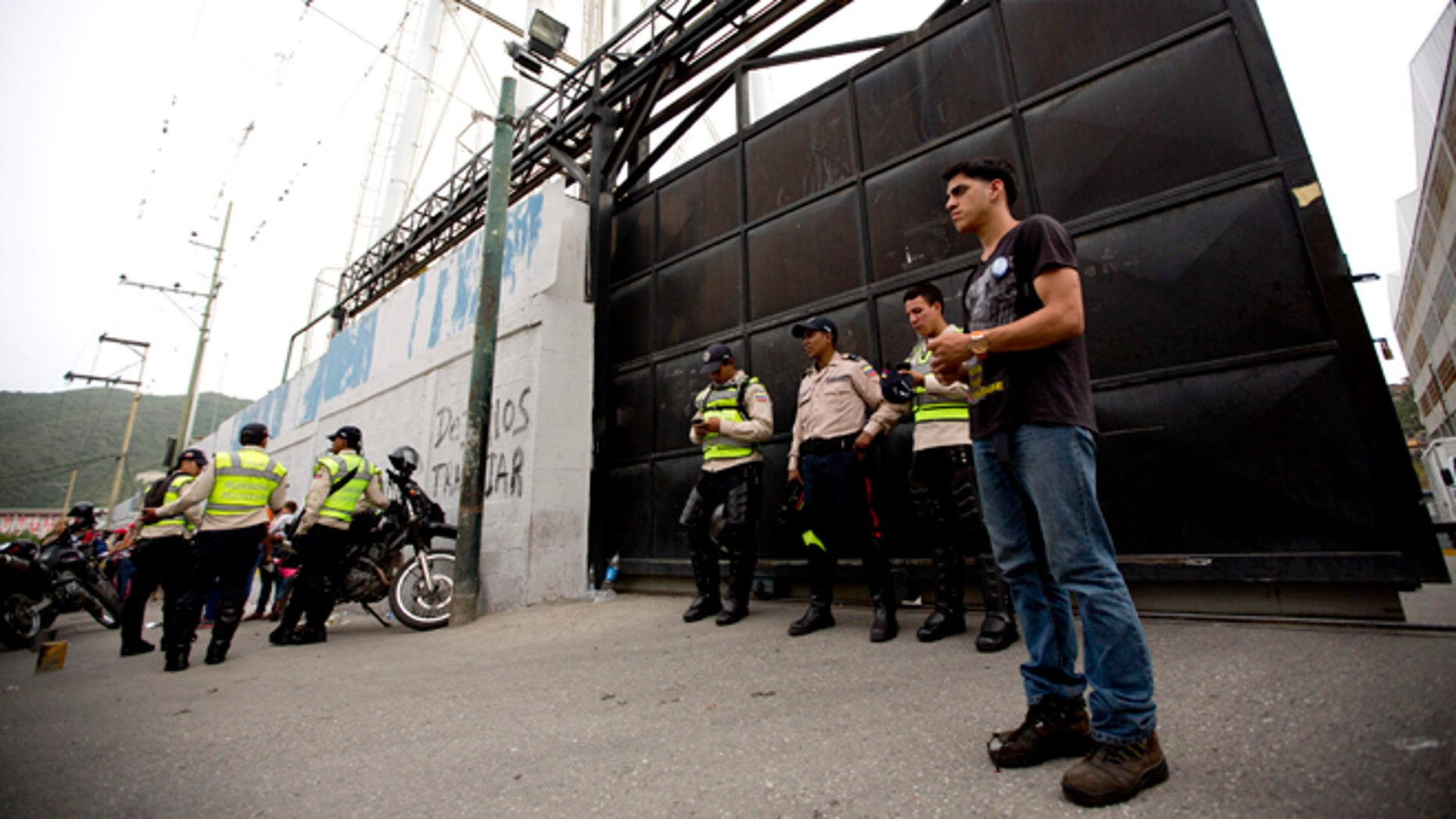 A group of Bolivarian Police officers stand at the gate of distribution center belonging to Venezuelas largest food company, Empresas Polar, in La Yaguara in Caracas, Venezuela, Thursday, July 30, 2015. According to Empresas Polar director Manuel Felipe Larrazabal the government occupied of one of its Caracas food distribution centers. President Nicolas Maduro has accused Polar of sabotaging the economy by hoarding goods and intentionally creating shortages, a charge the company has denied. (AP Photo/Ariana Cubillos)