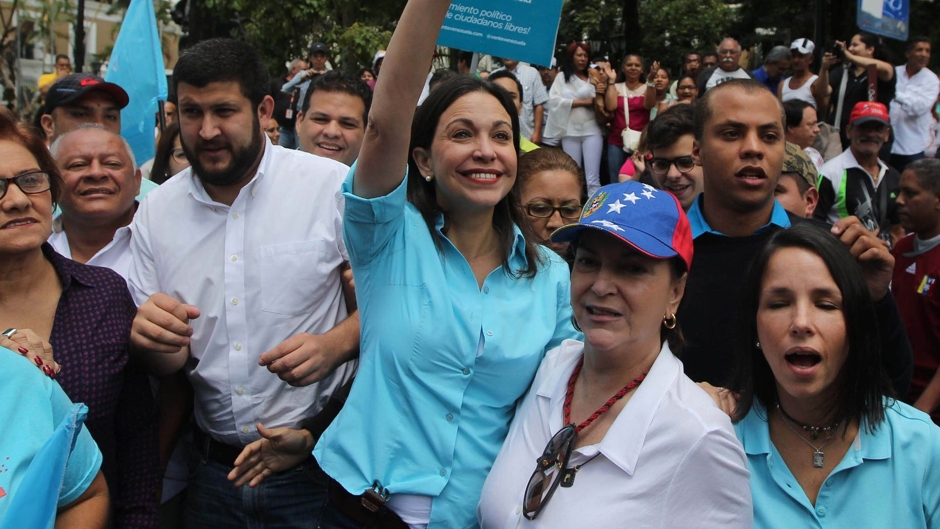 Monday, Aug. 3, 2015: Opposition leader Maria Corina Machado waves as she and her supporters arrive to the National Electoral Council (CNE) with the intention of registering her candidacy for congressional elections in Los Teques, Venezuela.