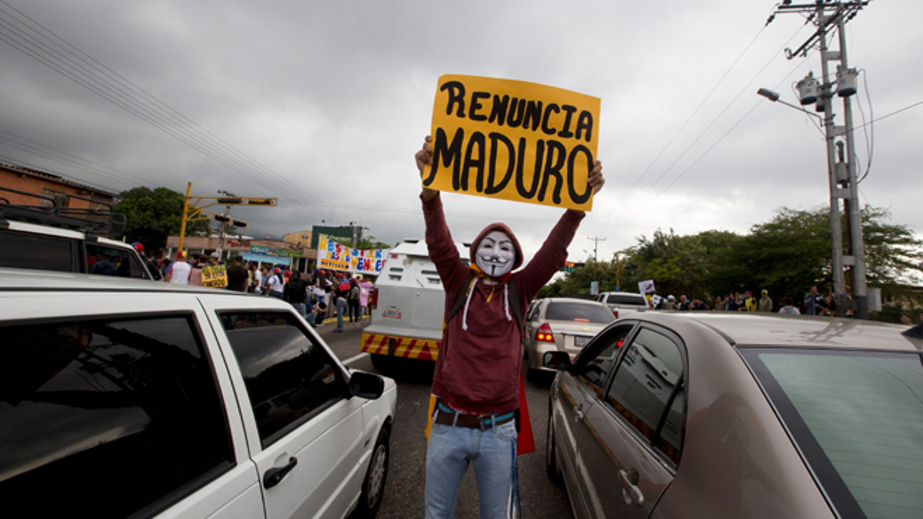 "FILE - In this Jan. 23, 2015, file photo, a demonstrator wearing a Guy Fawkes mask displays a poster that reads in Spanish ""Maduro Resign"" during a protest in San Cristobal, Venezuela. A crop of new candidates who raged in the streets against Venezuelas socialist administration last spring, are now putting their faith in the ballot box as a means to force President Nicolas Maduro from power. (AP Photo/Fernando Llano, File)"