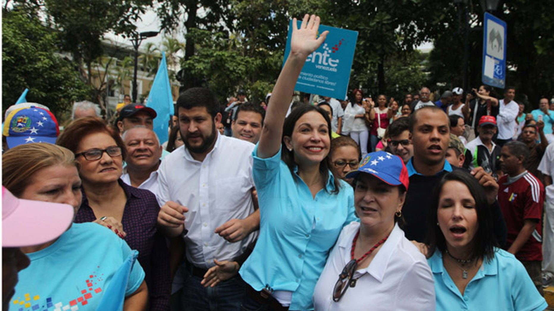 Opposition leader and former lawmaker Maria Corina Machado waves as she and her supporters arrive to the National Electoral Council (CNE) with the intention of registering Machado's candidacy for congressional elections in Los Teques, Venezuela, Monday, Aug. 3, 2015. Machado, who was not allowed to register on Monday, is among hardline leaders who called for President Nicolas Maduro to resign last year and helped lead sometimes bloody street protests demanding an end to the South American country's administration. The ruling party stripped her of her congressional seat amid the protests and barred her from holding public office. (AP Photo/Fernando Llano)