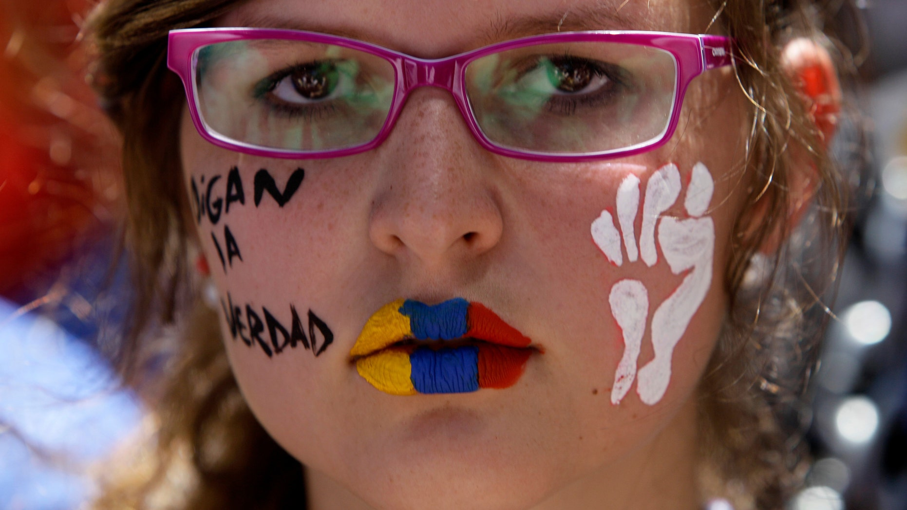 A demonstrator with her lips painted with the colors of the Venezuelan flag attends a protest in Caracas, Venezuela, Sunday, March 3, 2013. Hundreds of protesters took to the streets of Venezuela's capital on Sunday, demanding the government provide complete details about the health of ailing Venezuela's President Hugo Chavez. (AP Photo/Fernando Llano)