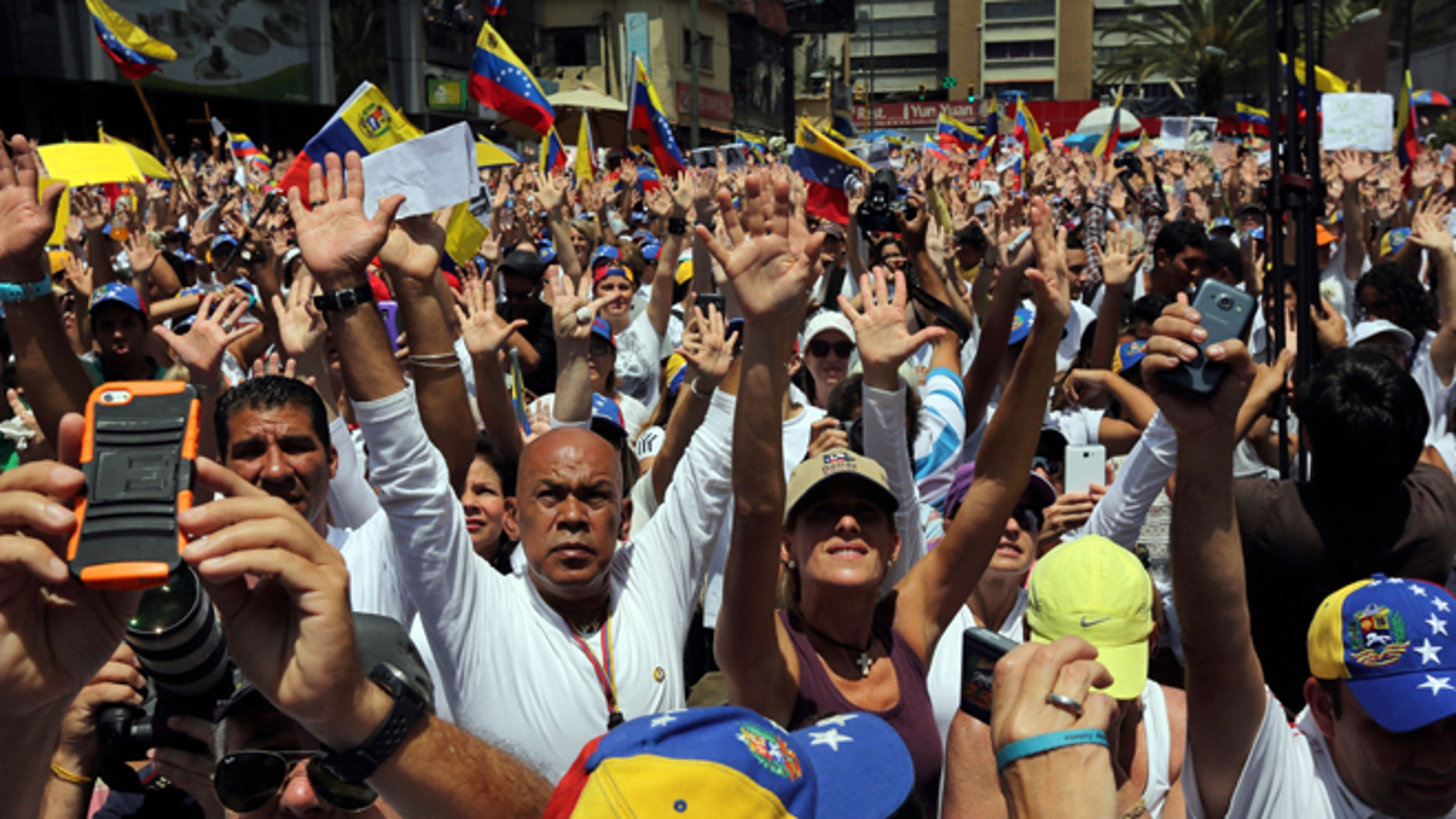 Demonstrators raise their arms in unison during a demonstration honoring the victims who died in last month's anti-government protests, in Caracas, Venezuela, Tuesday, March 4, 2014. Venezuelan opposition leader Henrique Capriles called Monday for citizens to begin organizing committees that could sustain the pressure that continuing street protests have placed on President Nicolas Maduro's government. (AP Photo/Fernando Llano)