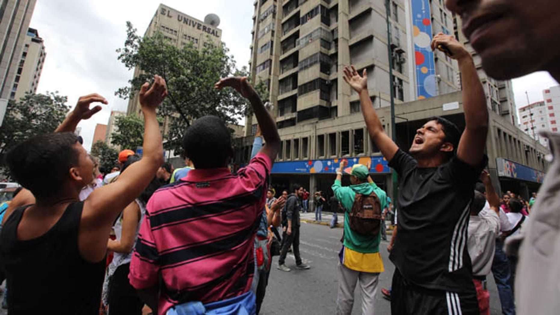 People call others in apartment and office buildings to join their protest demanding food, a few blocks from Miraflores presidential palace in Caracas, Venezuela, Thursday, June 2, 2016. Venezuela is seeing rising frustration with widespread food shortages and triple-digit inflation. (AP Photo/Fernando Llano)