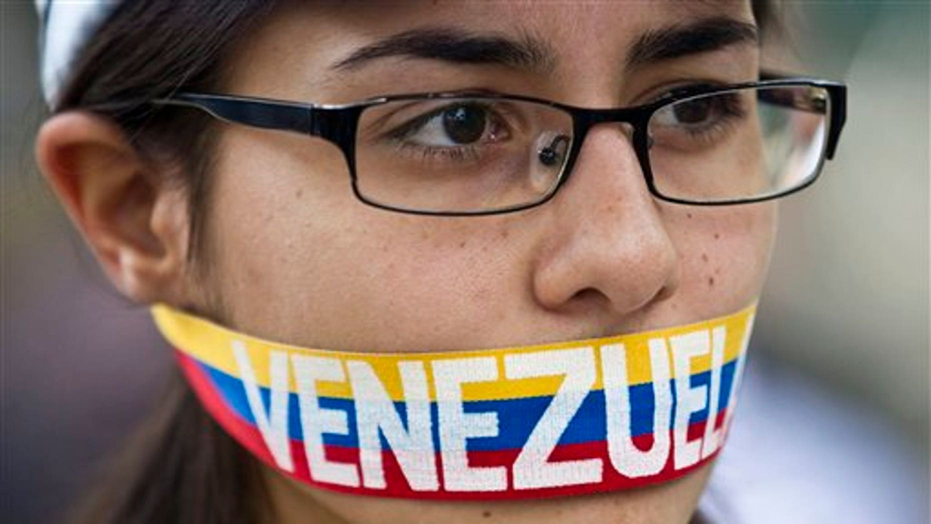 """An anti-government demonstrator stands with a tri-colored ribbon covering her mouth that reads """"Venezuela"""" during a protest in front of an office of the Organization of American States, OAS, in Caracas, Venezuela, Friday, March 21, 2014. Opposition lawmaker Maria Corina Machado is scheduled to speak before the OAS council in a closed-door session Friday in Washington D.C., presenting the situation in her country (AP Photo/Esteban Felix)"""