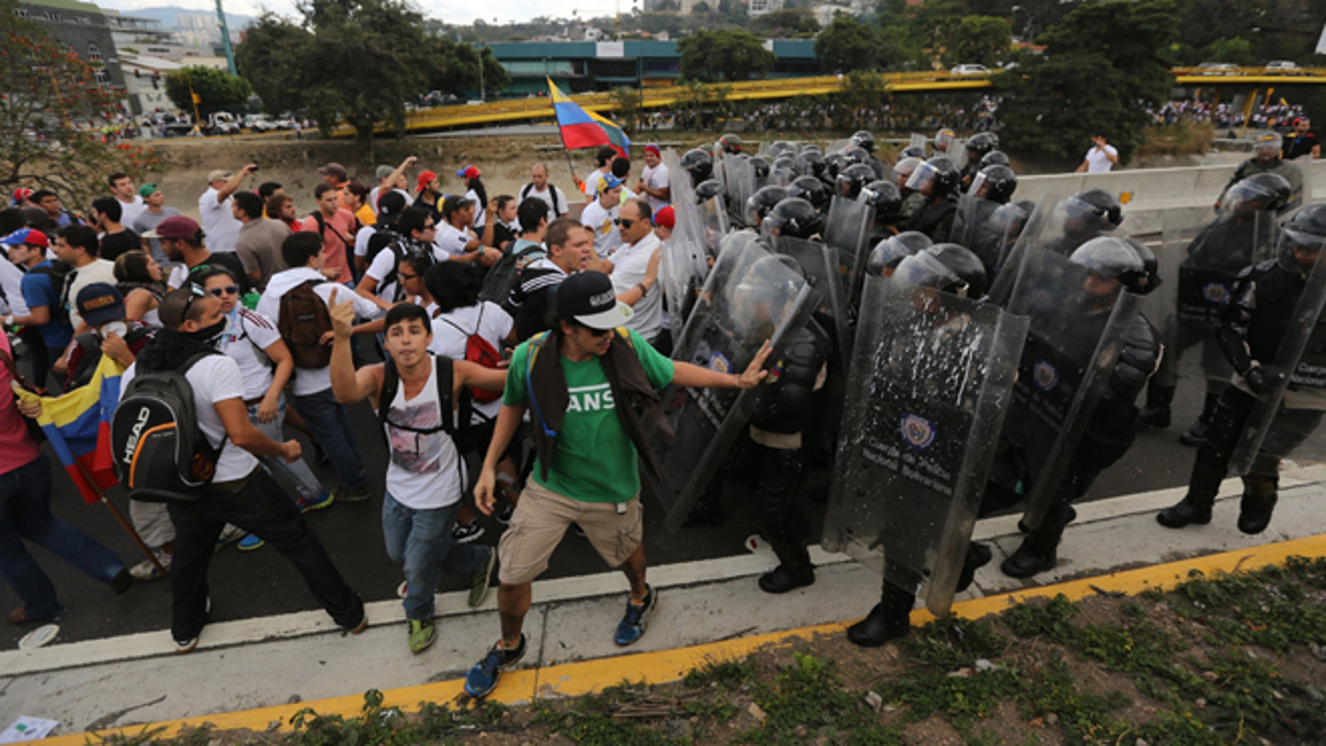 Bolivarian National Police officers push demonstrators to prevent them from blocking the Francisco Fajardo highway in Caracas, Venezuela, Thursday, Feb. 27, 2014. Anti-government protesters rallied to demand an end to the government crackdown on protests and the release of those jailed in recent weeks.  (AP Photo/Fernando Llano)