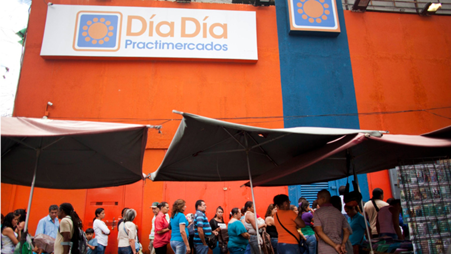 People line up outside the Dia a Dia supermarket after it was taken over by the government in the Propatria neighborhood of Caracas, Venezuela, Tuesday, Feb. 3, 2015. The government is temporarily taking over the Dia a Dia supermarket chain as part of a crackdown on private businesses it blames for worsening shortages and long lines. Popular items with government fixed prices that have been running short are coffee, cooking oil, precooked corn flour, sugar, milk, toilet paper, disposable diapers, detergent and fabric softener, among other items. (AP Photo/Ariana Cubillos)