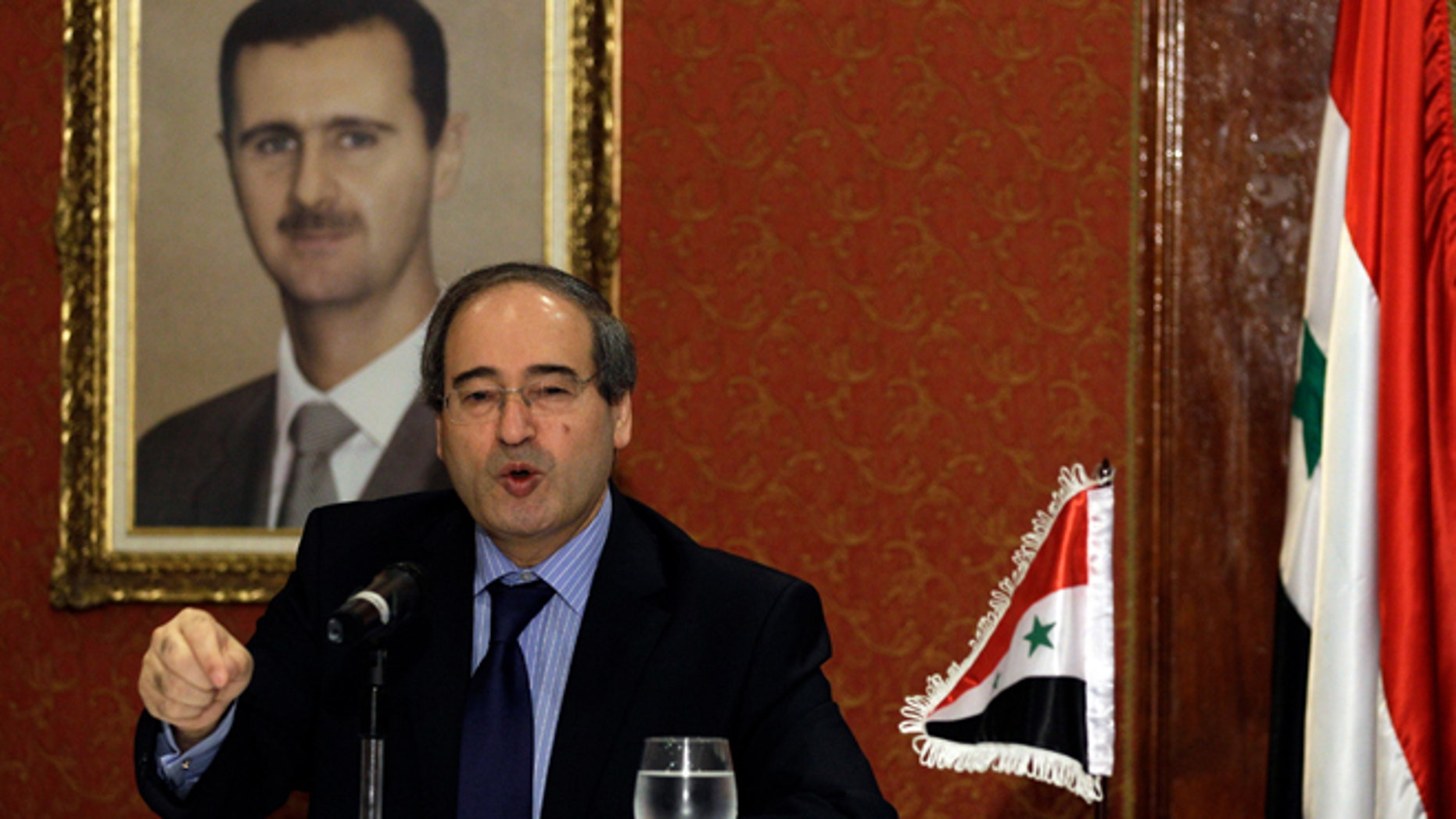Backdropped by a framed picture of Syrian President Bashar al-Assad, Syria's Deputy Foreign Minister Faisal al-Mokdad speaks during a news conference at a local hotel in Caracas, Venezuela, Tuesday, Nov. 27, 2012. T(AP Photo/Fernando Llano)