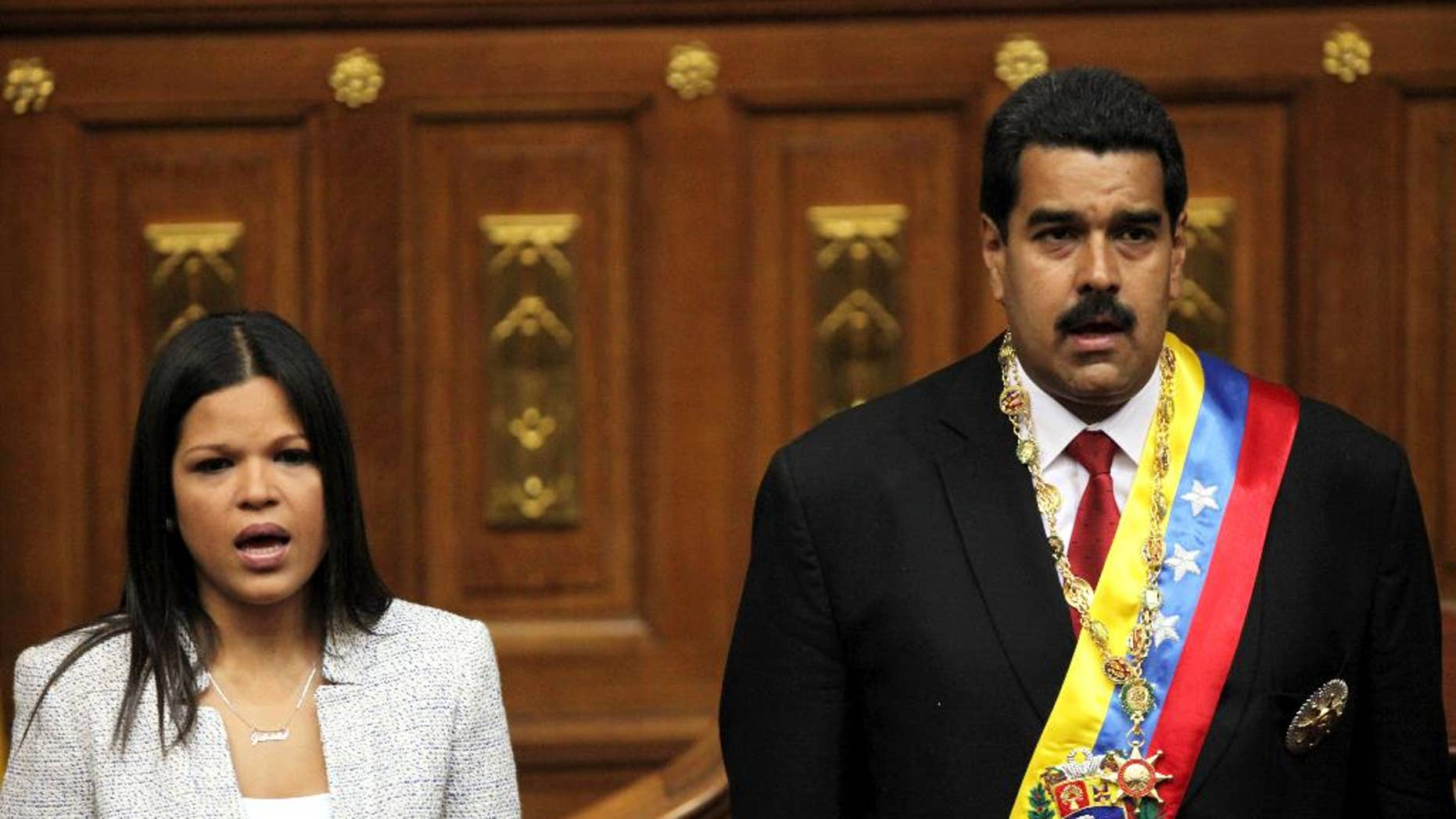FILE - In this April 19, 2013 file photo, daughter of the late Hugo Chavez, Maria Gabriela Chavez and Venezuela's newly sworn-in President Nicolas Maduro, join in the singing of their national anthem in the National Assembly, in Caracas, Venezuela. In a July 23, 2014 closed-door meeting July at U.N. headquarters in New York, Venezuela quietly secured the backing of Latin America and the Caribbean to obtain a seat on the United Nations Security Council. Maria Gabriela Chavez is Venezuela's alternate ambassador to the U.N. (AP Photo/Fernando Llano, File)
