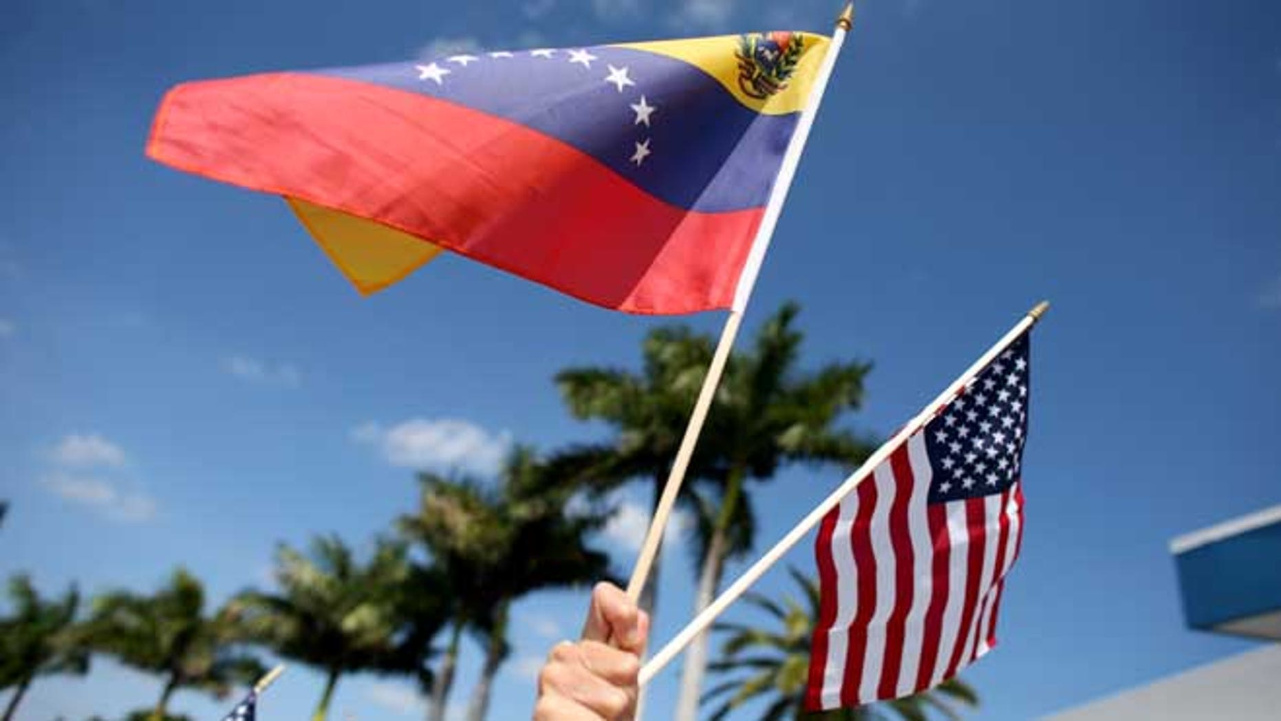 MIAMI, FL - MARCH 01:  A protester holds a Venezuelan and American flag as she and other Venezuelans and their supporters show their support for the anti-government protests in Venezuela on March 1, 2014 in Miami, Florida.  (Photo by Joe Raedle/Getty Images)
