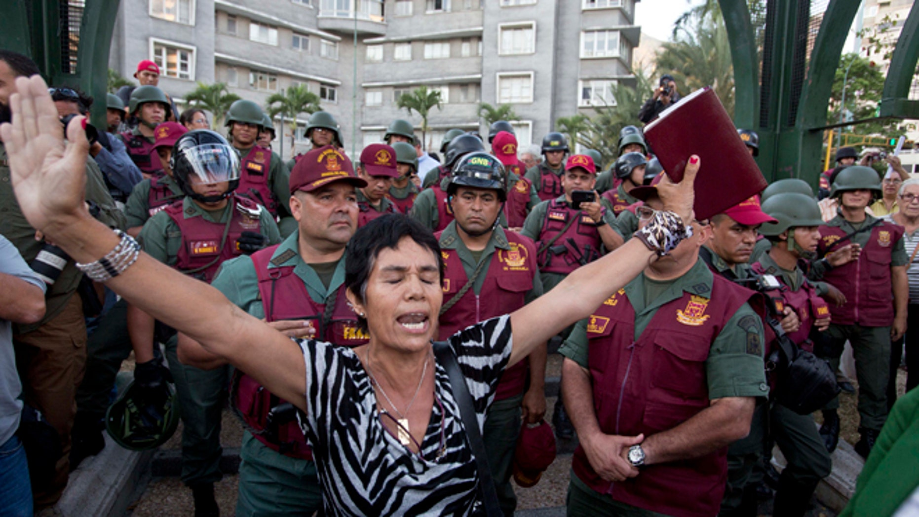 A woman prays with a bible in her hand, in front of Bolivarian National Guard officers during an anti-government protest in Plaza Altamira, Caracas, Venezuela, Tuesday, March 18, 2014. Protesters blocked the streets only when traffic lights turned red under the watchful gaze of the National Guard. Security forces have taken control of the plaza that has been at the heart of anti-government protests that have shaken Venezuela for a month. (AP Photo/Esteban Felix)