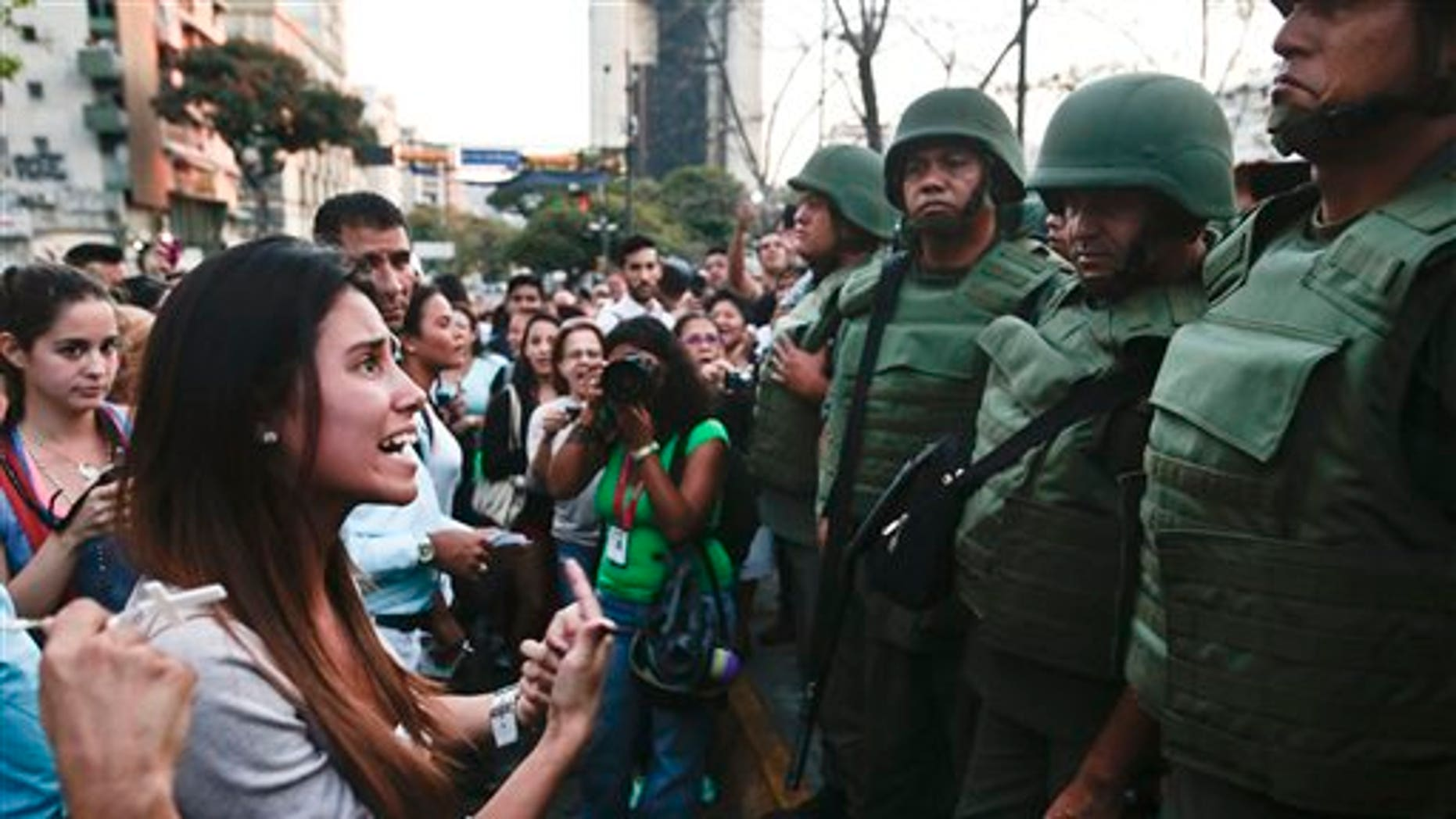 An anti-government protester argues with Bolivarian National Guards in Plaza Altamira in Caracas, Venezuela, Monday, March 17, 2014. Security forces on Monday took control of a Caracas plaza that has been at the heart of anti-government protests that have shaken Venezuela for a month. (AP Photo/Esteban Felix)
