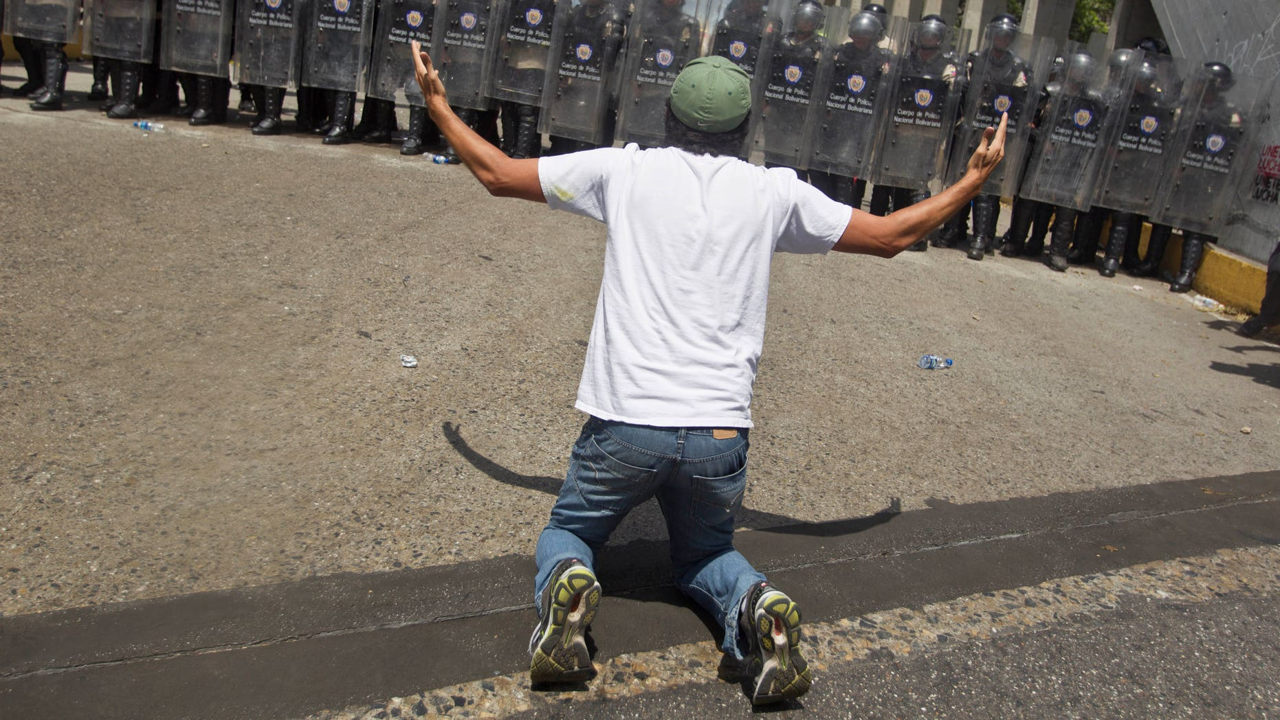 An anti-government demonsrator kneels in front of a formation of Bolivarian National Police in riot gear, during clashes at the Central University of Venezuela, UCV, in Caracas, Venezuela, Thursday, March 20, 2014. Thursday dawned with two more opposition politicians, San Cristobal Mayor Daniel Ceballos and San Diego Mayor Enzo Scarano, behind bars. Police used tear gas and water cannons to disperse a student-called protest of several thousand people in Caracas, some of those demonstrating against the arrests of the mayors. (AP Photo/Esteban Felix)