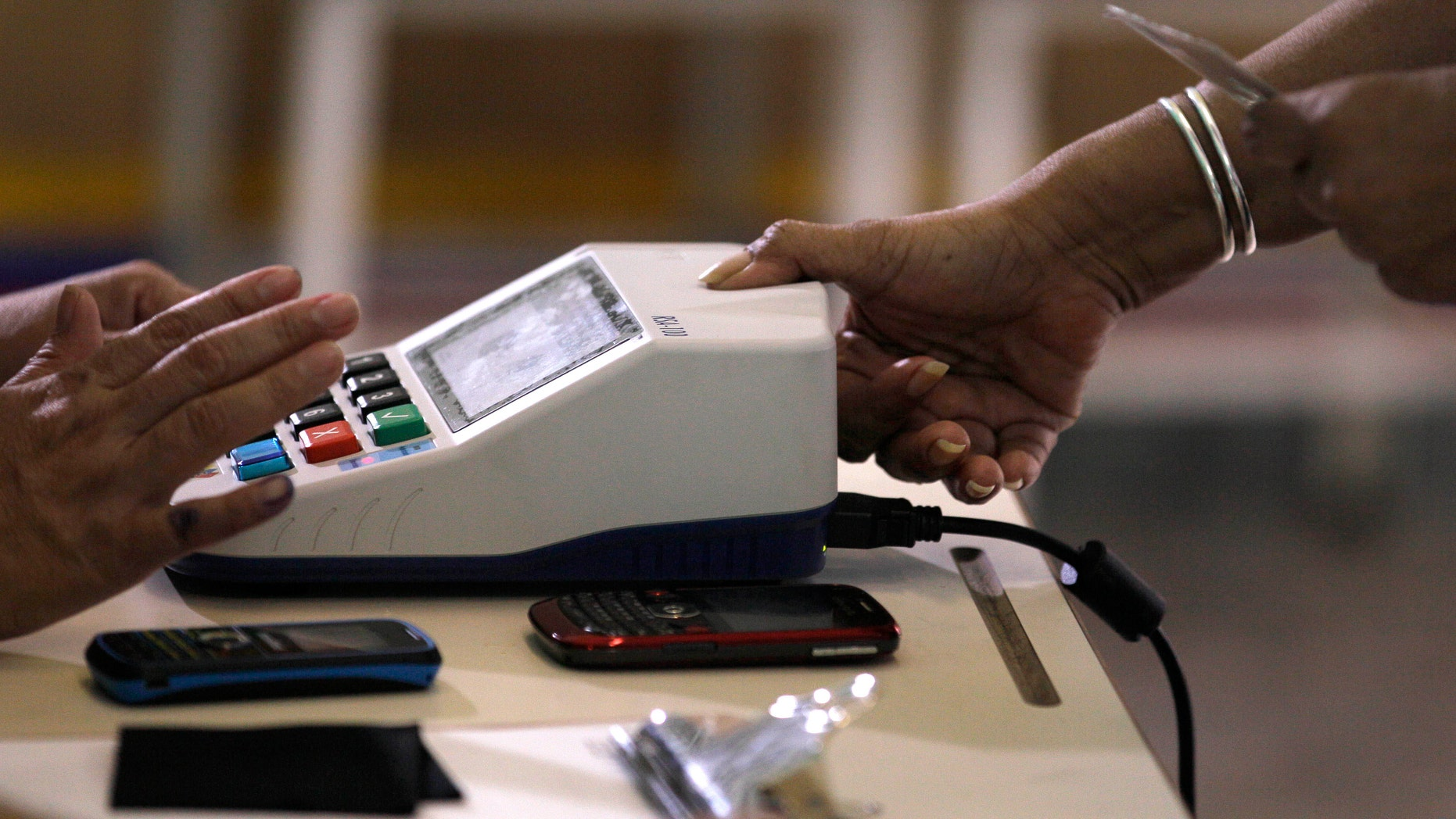 A voter uses a fingerprint scanner during a mock election to simulate upcoming Oct. 7 presidential election at a polling station in Caracas, Venezuela, Sunday, Aug. 5, 2012. (AP Photo/Fernando Llano)