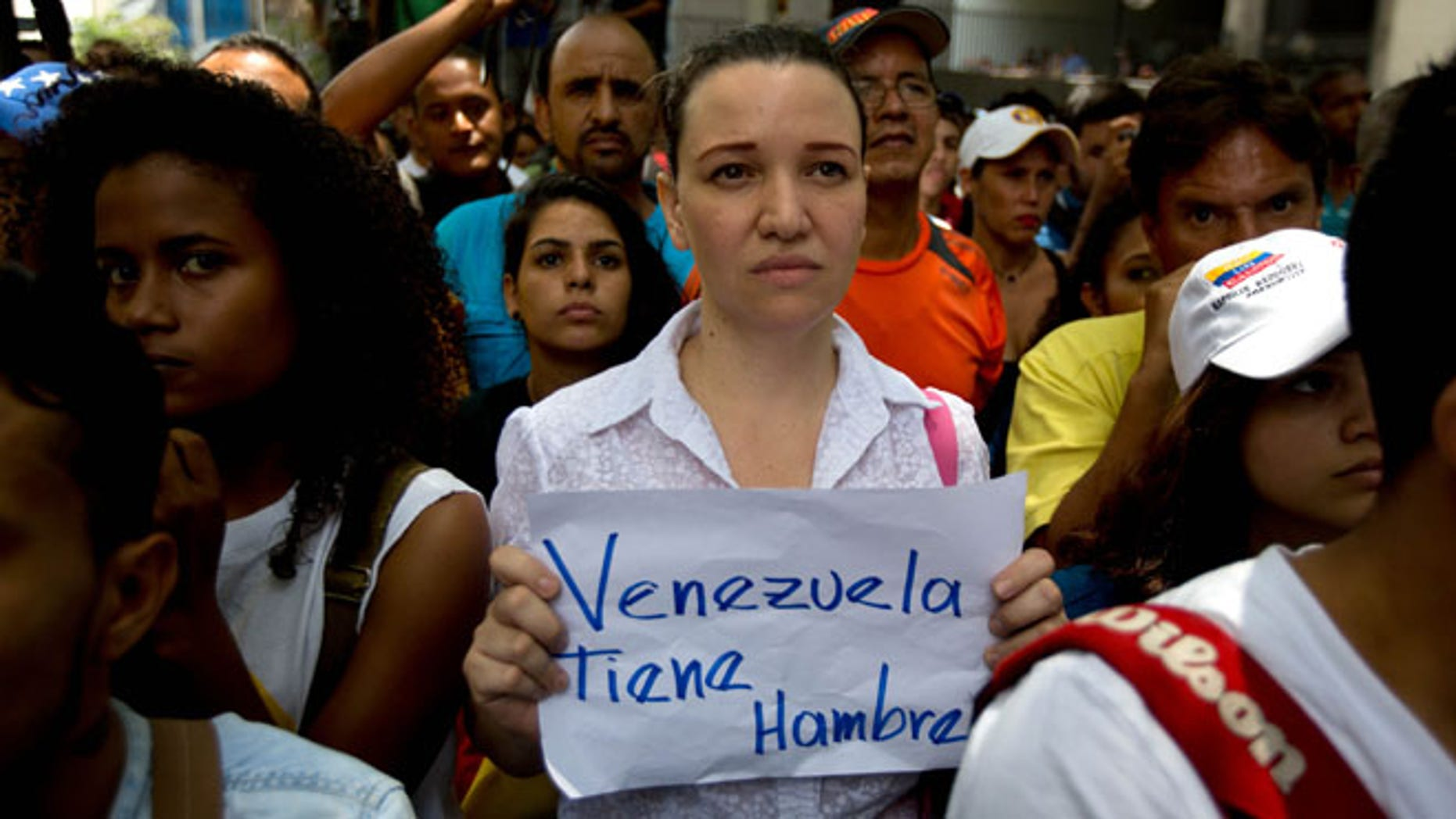 "An opposition members holds a handwritten message that that reads in Spanish; ""Venezuela is hungry,"" during a protest outside the court offices of the Chacao municipality, in Caracas, Venezuela, Wednesday, May 25, 2016. Opposition members held a demonstration to demand authorities hold a recall referendum on cutting short Nicolas Maduro's presidency. (AP Photo/Fernando Llano)"