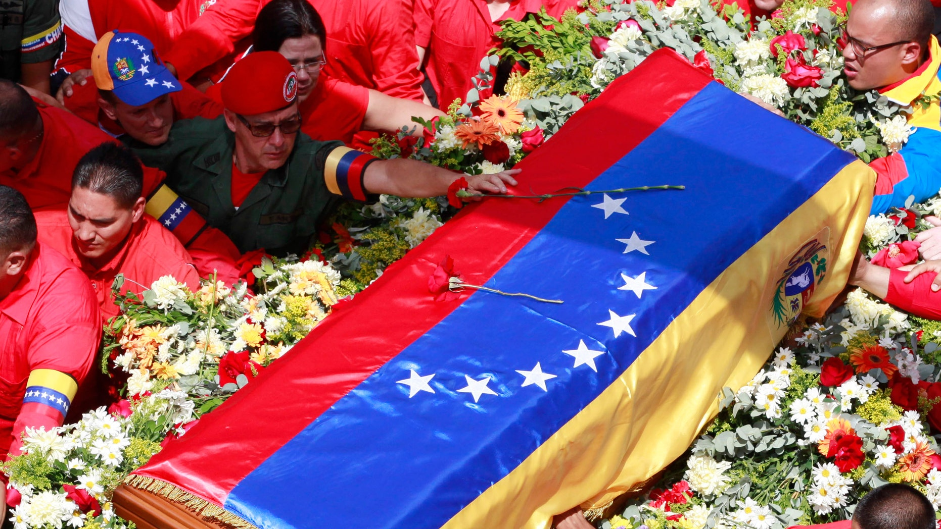 A member of the presidential guard, top, places a flower on the coffin containing the body of late President Hugo Chavez.