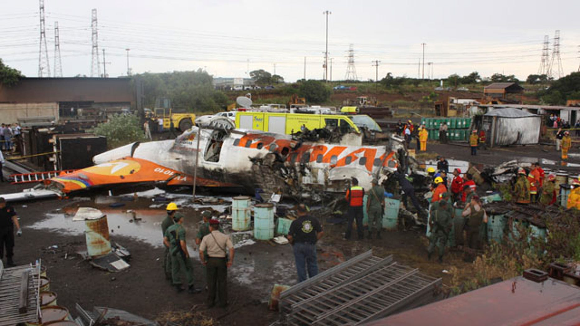 People stand around the wreckage of a state-run Conviasa airline plane after it crashed into a lot used by the state-run Sidor steel foundry near Puerto Ordaz, Venezuela, Monday Sept. 13, 2010.