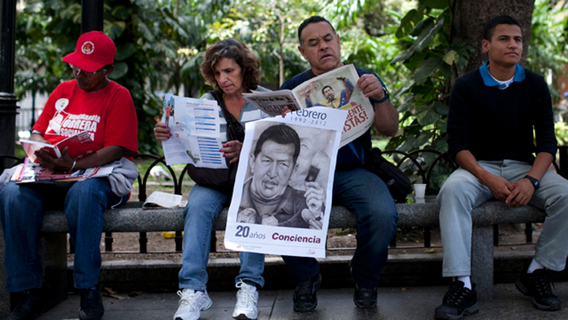 Feb. 28: A man holds a poster of Venezuelas President Hugo Chavez as he reads a paper in Bolivar Square in Caracas.