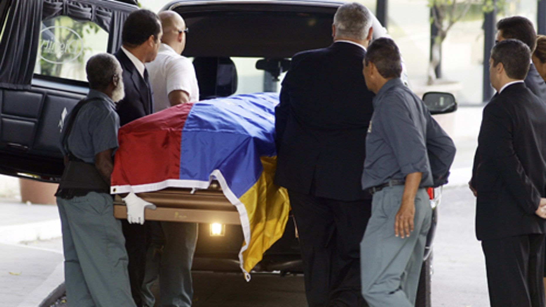 Workers carry the body of former Venezuelan President Carlos Andres Perez from the mausoleum to the hearse in Miami. Perez is finally going home, more than nine months after he died living in exile in Miami.