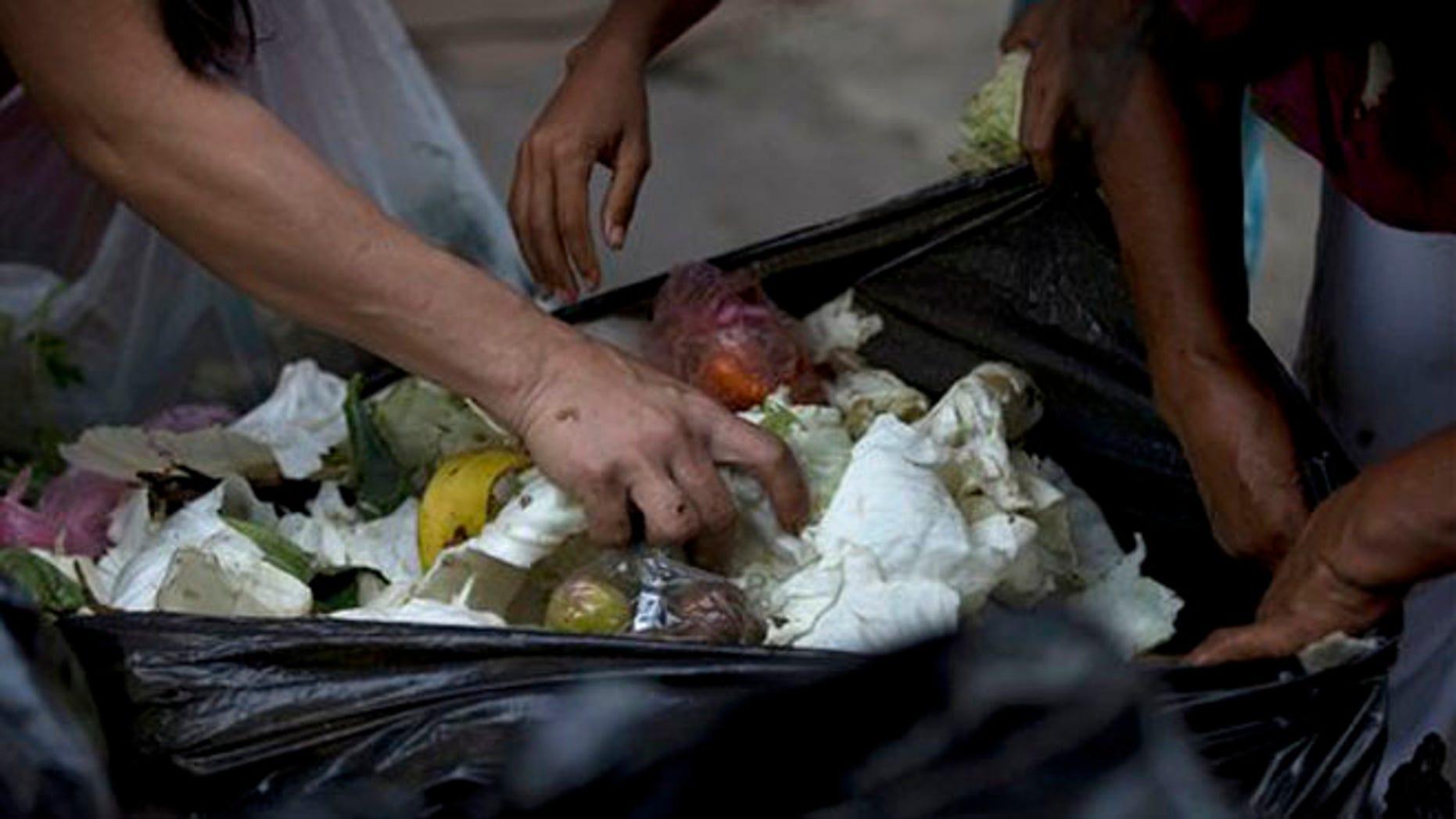 En esta imagen, tomada el 2 de junio de 2016, varias personas revisan bolsas de basura en busca de frutas y verduras en el exterior de un supermercado en el centro de Caracas, en Venezuela. A las personas desempleadas que buscan comida entre los alimentos que tiran las tiendas suelen unirse ahora propietarios de pequeños negocios, estudiantes universitarios o jubilados, personas que se consideran dentro de la clase media. El nivel de vida se ve afectado desde hace tiempo por una inflación de tres dígitos y escasez de alimentos, algo que lleva a muchos a recurrir a la agricultura urbana para devolver las verduras a su dieta. (AP Foto/Fernando Llano)