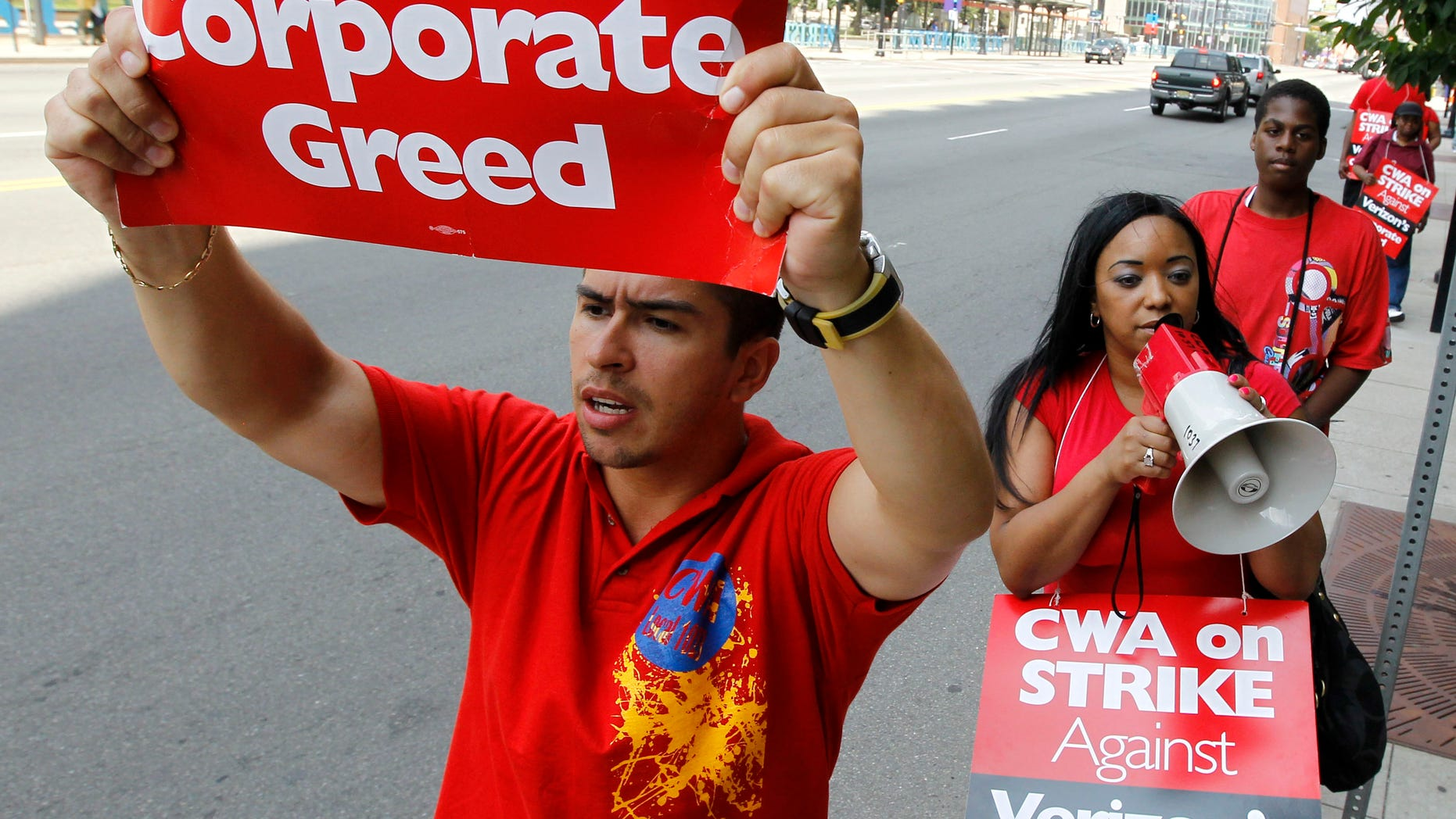 Ferdinand Hernandez, left, a sales associate who works for Verizon in Newark, N.J., holds a sign as he and coworker Leyda Jimenez, center, a multilingual consultant, picket outside of a Verizon store, Monday, Aug. 8, 2011, in Newark, N.J.