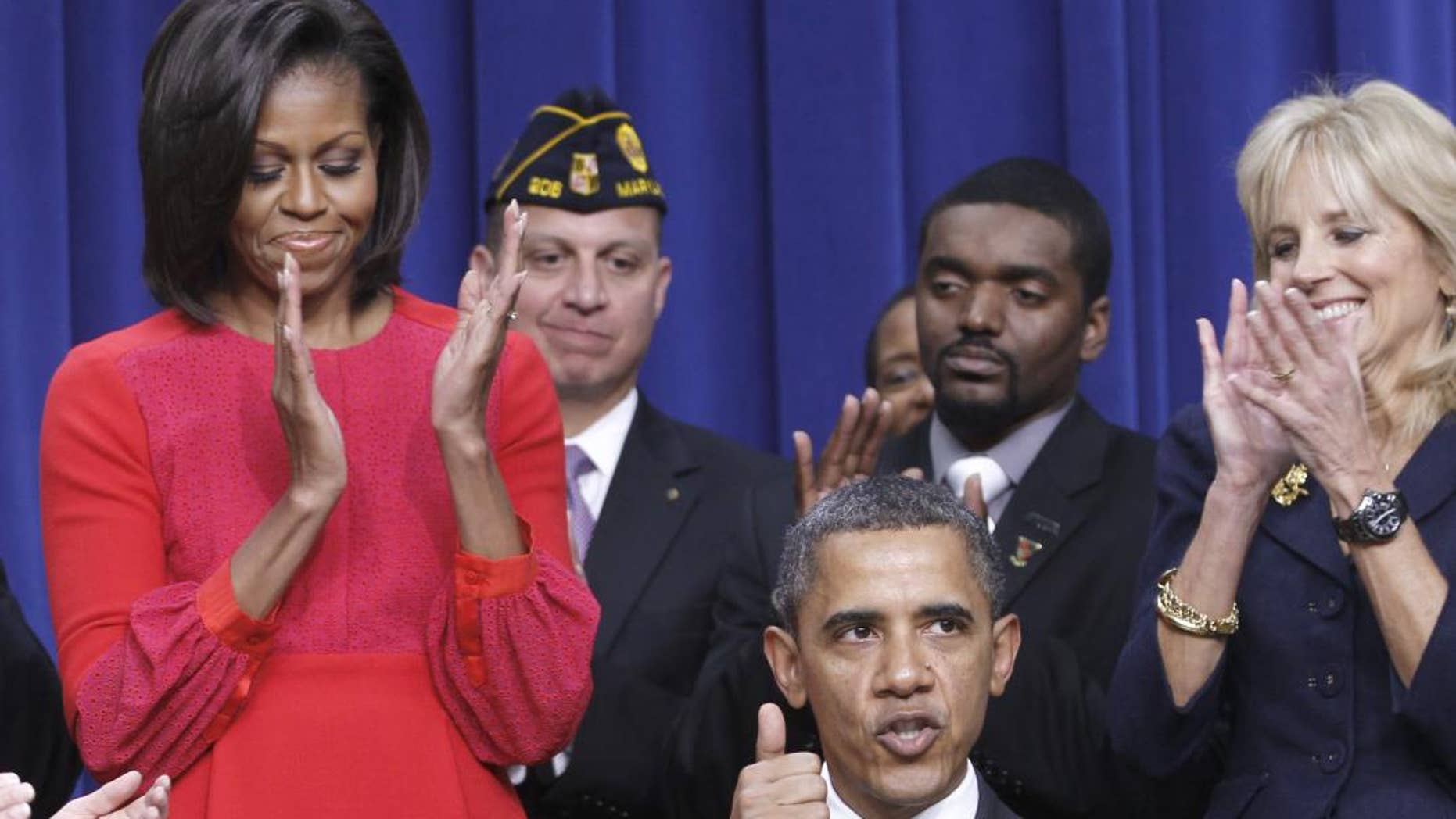 President Barack Obama give a 'thumbs-up' after signing legislation that will provide tax credits to help put veterans back to work, Monday, Nov. 21, 2011, during a ceremony at the Eisenhower Executive Office Building on the White House complex in Washington. The president is joined by first lady Michelle Obama, and Dr. Jill Biden. (AP Photo/Pablo Martinez Monsivais)