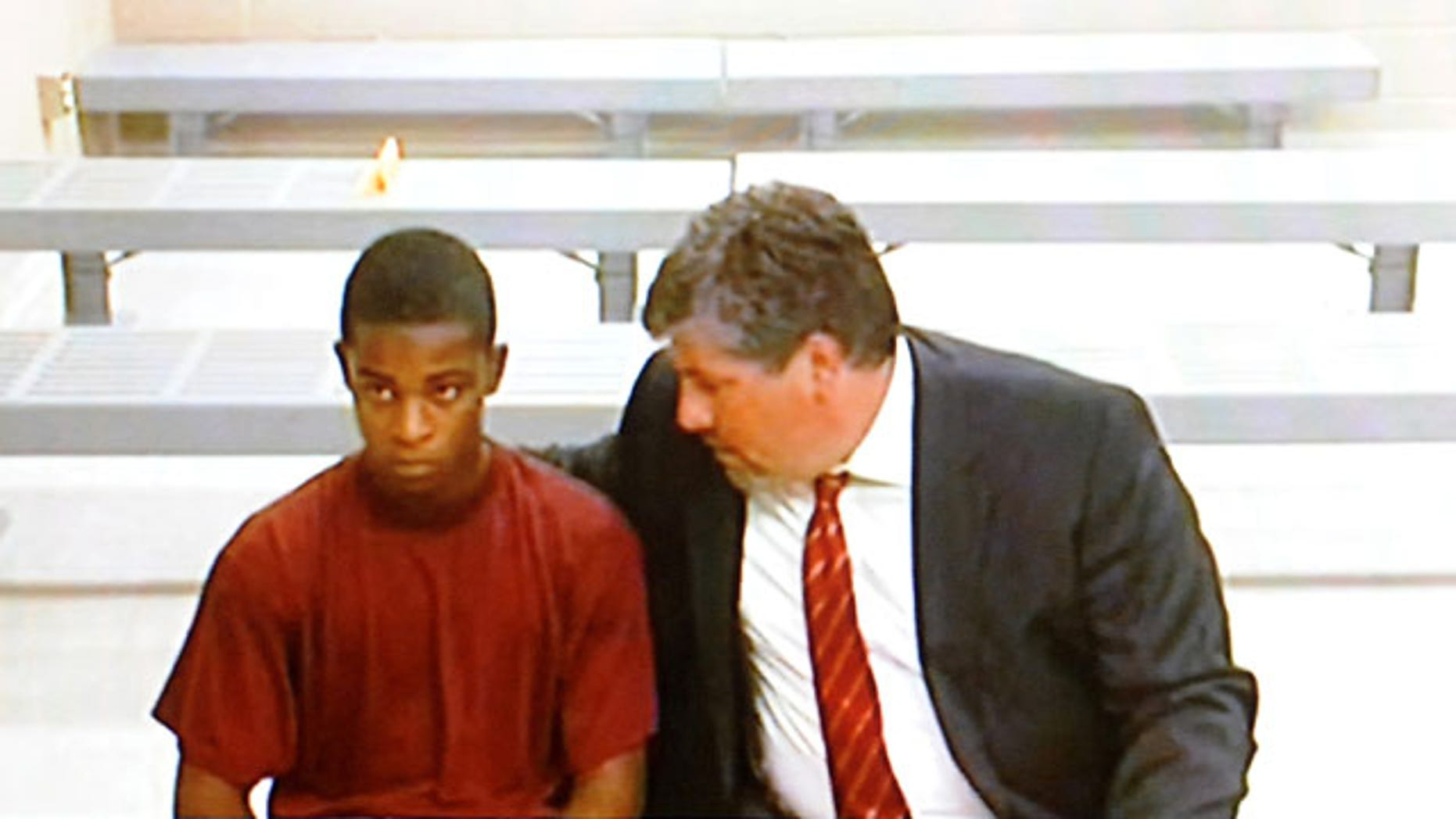 August 26, 2013: Demetrius Glenn, left, a teen that allegedly took part in the robbery and beating of 88-year-old World War II veteran Delbert Belton, listens to his lawyer, Christian J. Phelps, before a first appearance via video teleconference in District Court in Spokane, Wash. Glenn, who will be charged as an adult, is charged with first-degree murder and first-degree robbery and was ordered held on $2 million bail. (AP Photo/The Spokesman-Review)