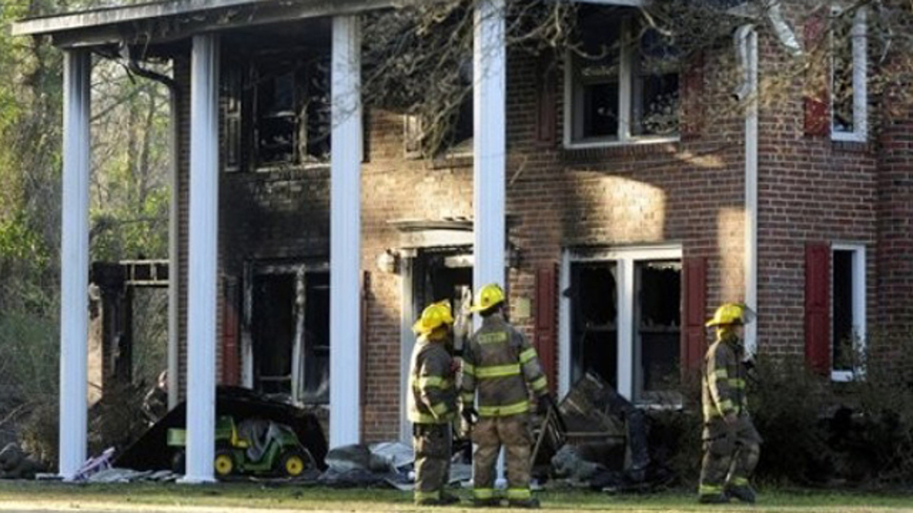 Mar. 6, 2012: Firefighters look at the front of a heavily damaged two- story home where a Special Forces soldier died trying to rescue his 2 small children during a house fire.
