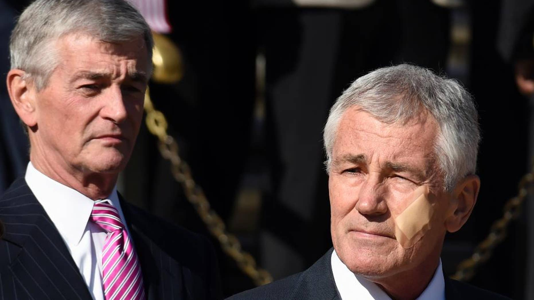 Defense Secretary Chuck Hagel, right, and Army Secretary John McHugh attend a wreath laying ceremony at the Tomb of the Unknowns, Tuesday, Nov. 11, 2014, at Arlington National Cemetery in Arlington, Va. in honor of Veterans Day. Hagel sports a bandage on his cheek after a minor kitchen mishap needing no stitches. (AP Photo/Susan Walsh)