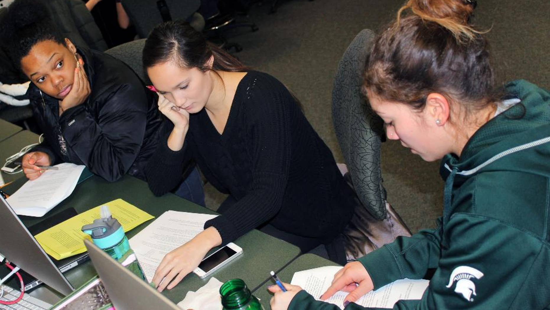 """In this March 1, 2015 photo released by Joe Grimm, Michigan State University students Tiara Jones, from left, Madeline Carino and Lia Kamana work on a new book """"100 Questions and Answers About Veterans"""" in East Lansing, Mich. The new book, researched and written by a Michigan State journalism class with assistance from former servicemen and women, is aimed at clearing up myths and misunderstandings held by some civilians.  (AP Photo/Joe Grimm)"""