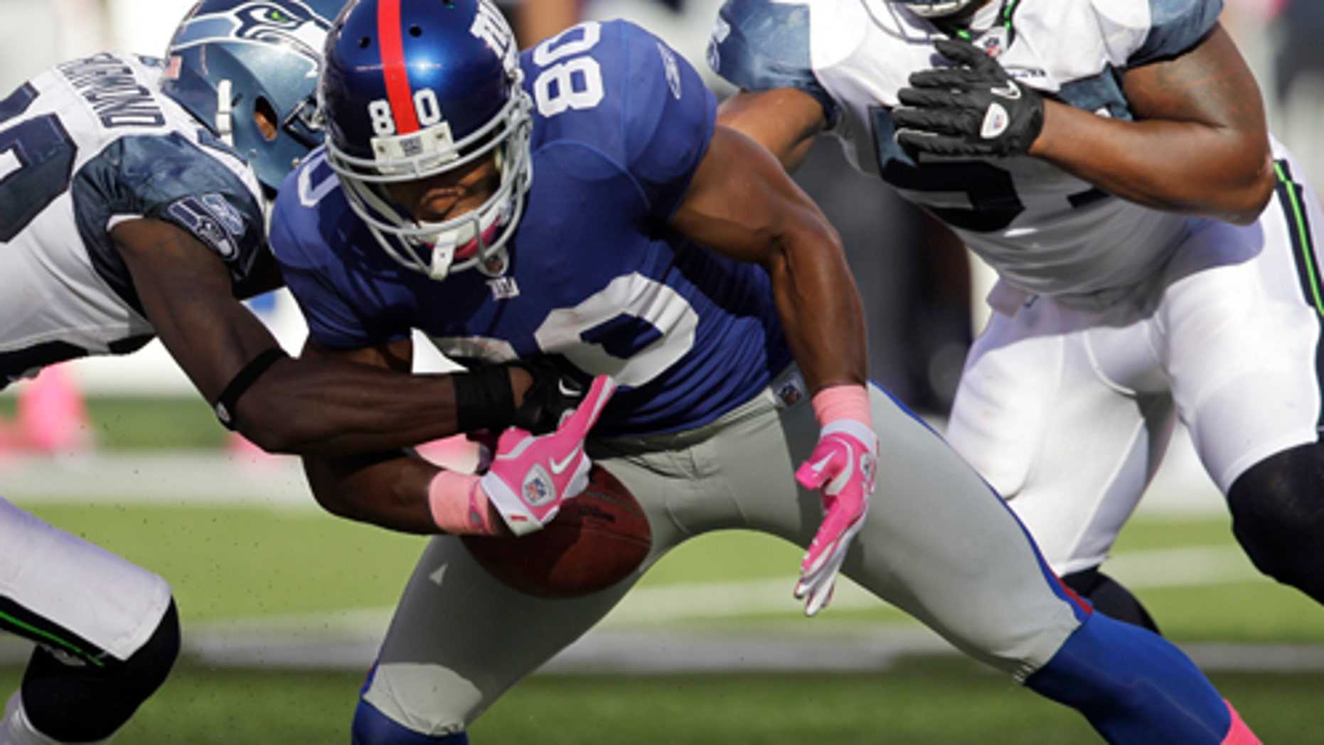 New York Giants wide receiver Victor Cruz (80) fumbles the ball as he is tackled by Seattle Seahawks defensive back Walter Thurmond (28) during the fourth quarter of an NFL football game Sunday, Oct. 9, 2011, in East Rutherford, N.J. The Seahawks won the game 36-25. (AP Photo/Julio Cortez)