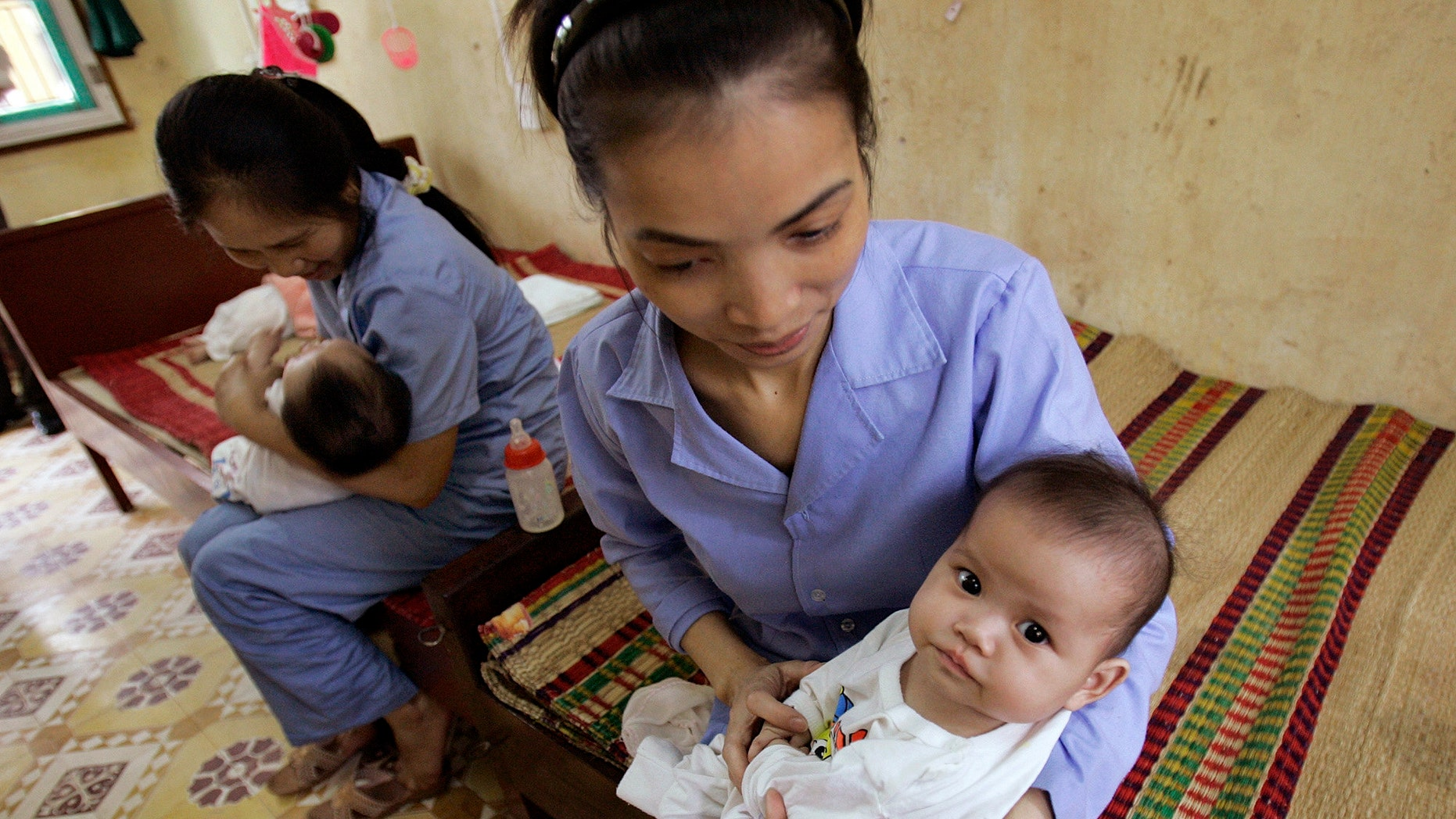 April 23, 2008 FILE photo of 5-month-old baby girls cradled by workers at an orphanage in Bac Ninh province, near Hanoi, Vietnam. Vietnam and the US will soon resume limited inter-country adoptions, 6 years after an imposed ban because of allegations of widespread baby-selling and children offered without the consent of birth parents.