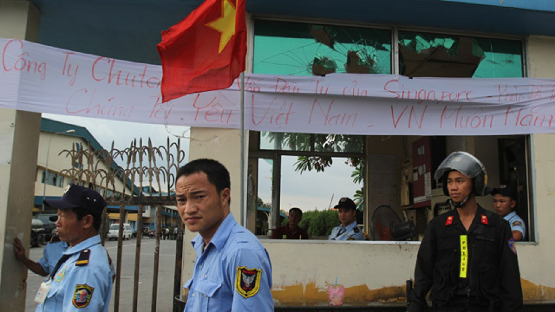 May 17, 2014: Security staff guard the entrance to a Singaporean factory in an industrial park in Binh Duong province, Vietnam after mobs attacked foreign owned factories following anti-China protests. (AP Photo/Hau Dinh)