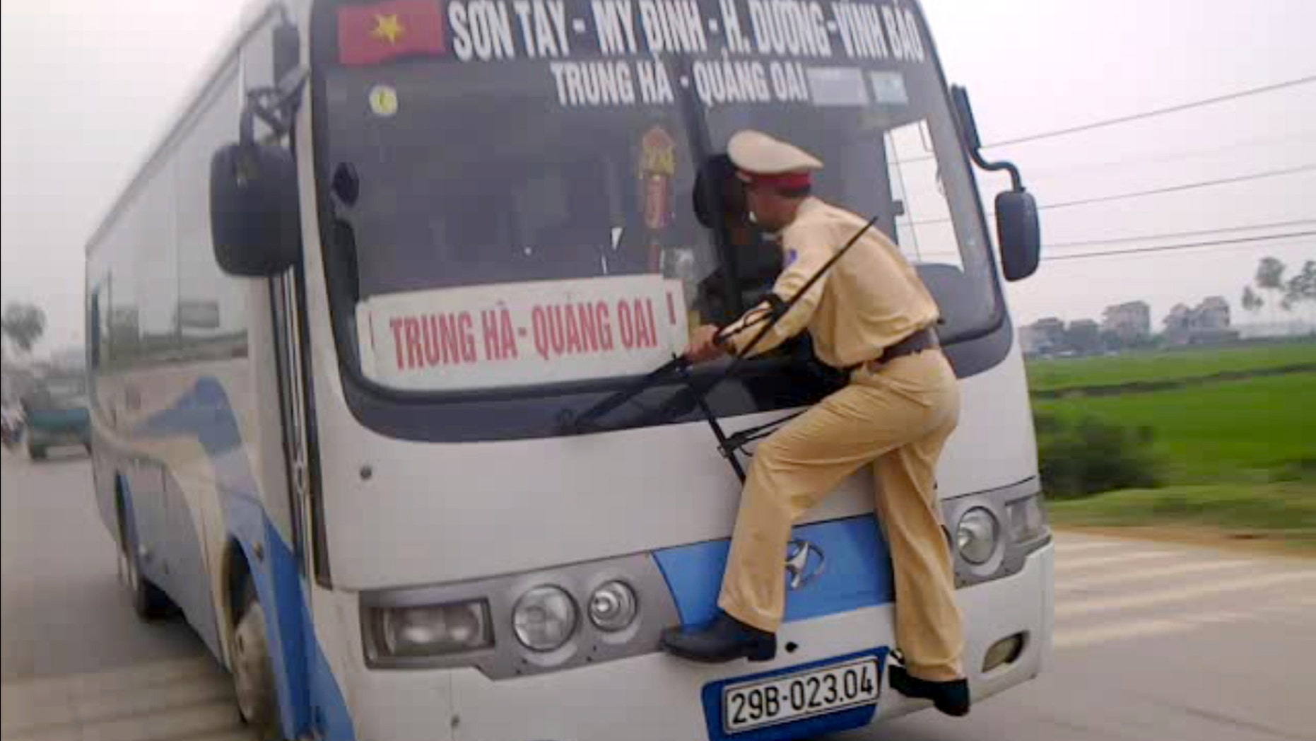 April 9, 2012: In this photo made from a video filmed and released by Hanoi Police, Vietnamese traffic police 2nd Lt. Nguyen Manh Phan clings on to the windshield wipers of a moving bus as he goes on a wild ride for nearly a 0.62 miles after the rogue driver tried to avoid a ticket in Ba Vi District outside Hanoi, Vietnam.