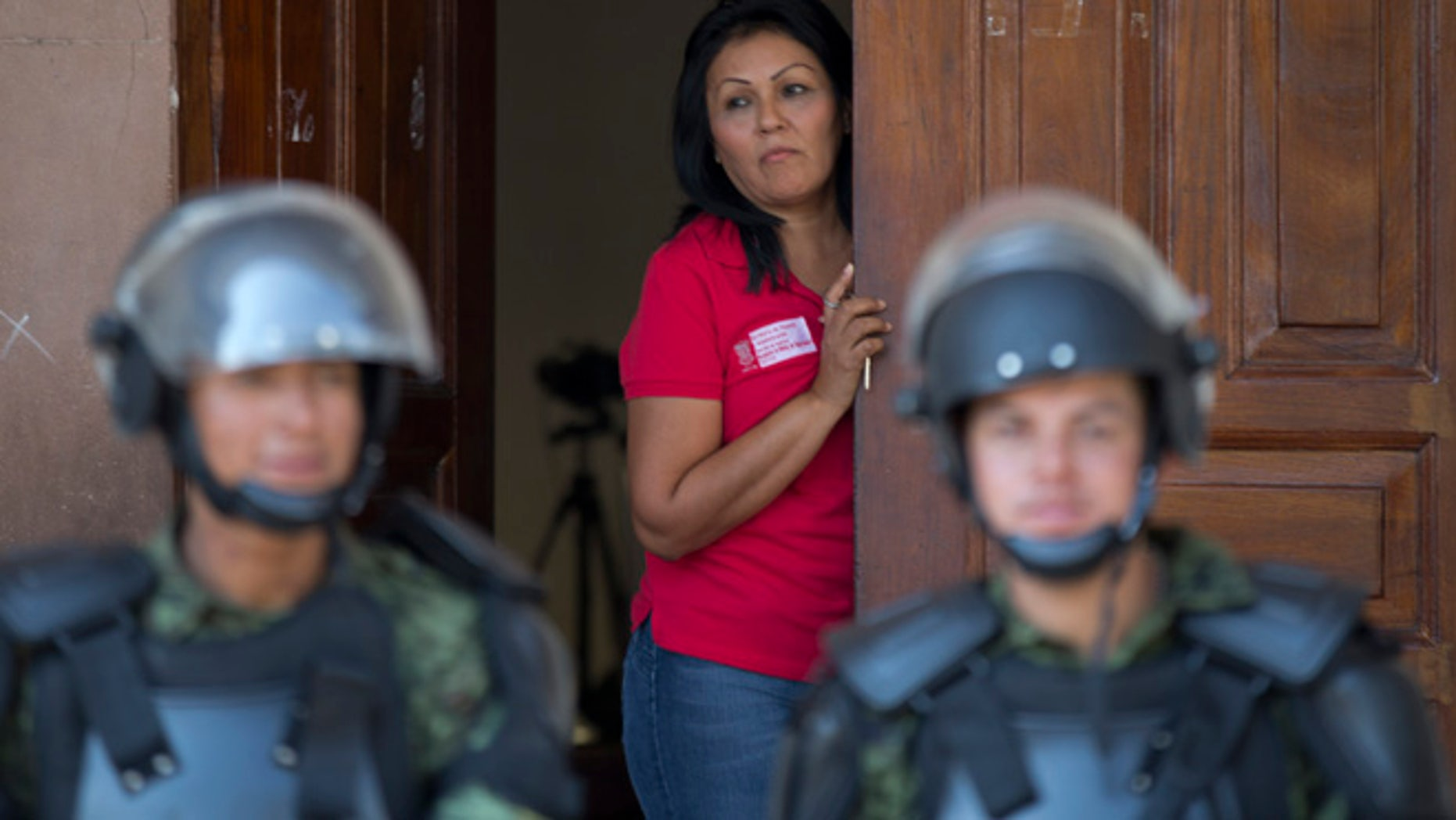 Jan. 14: A city employee looks out from a City Hall Hall doorway as a cordon of soldiers guard the government building in Apatzingan, Mexico. Mexican soldiers and federal police kept a tense standoff with vigilantes Tuesday after a new government campaign to stop violence in the western Michoacan state turned deadly.
