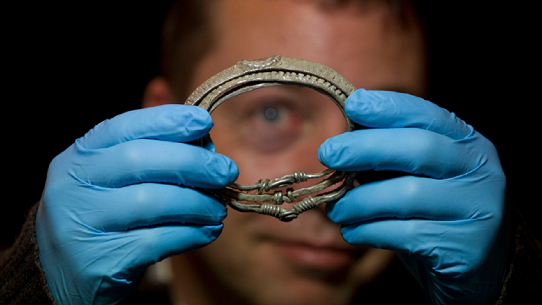 Dec. 14, 2011: Metal detectorist Darren Webster poses with a Viking arm-ring he discovered, estimated to date back to the late ninth or early tenth century, at the British Museum in London. The arm-ring is part of the Silverdale Viking Hoard discovered by Webster in September 2011 in the Silverdale area of North Lancashire, England. It comprises 201 silver objects including arm-rings, coins, finger-rings, ingots, brooch fragments and a fine wire braid.