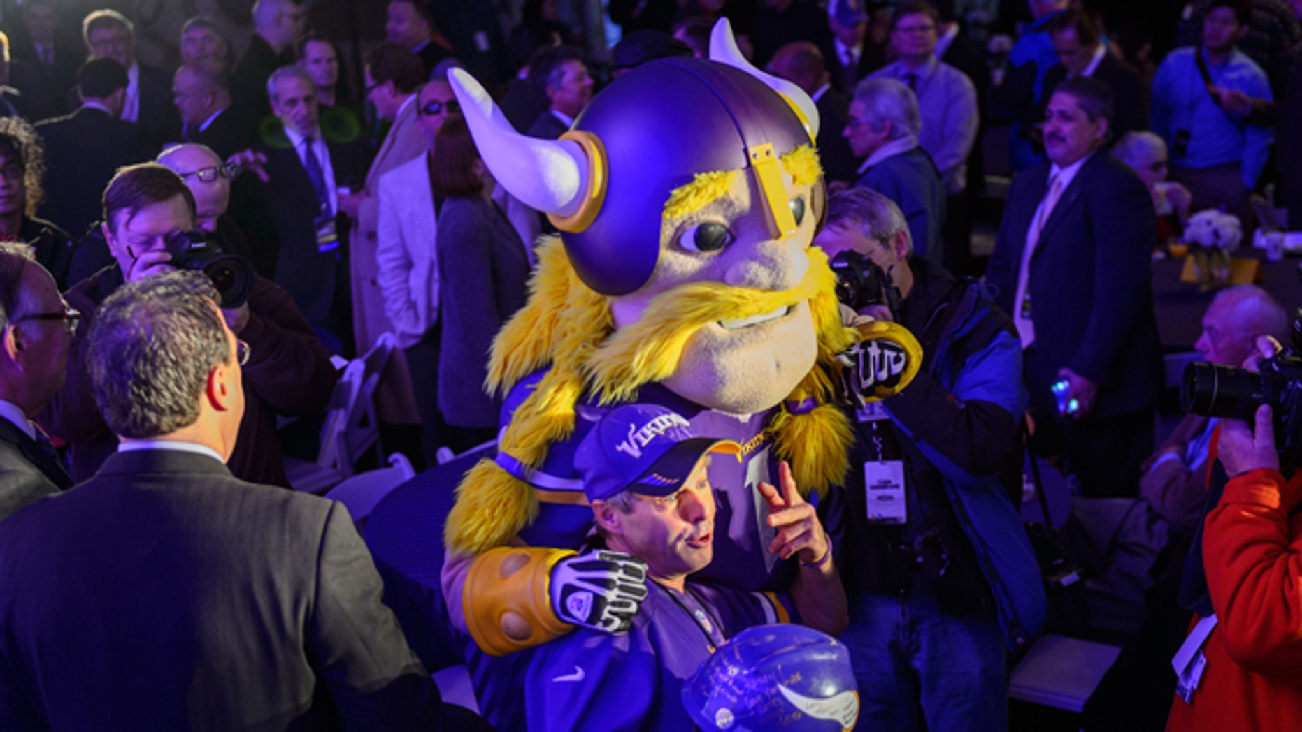 FILE: Dec. 3, 2013: A Minnesota Vikings fan with the team mascot during the groundbreaking ceremony for the new Vikings stadium, in Minneapolis, Minn.