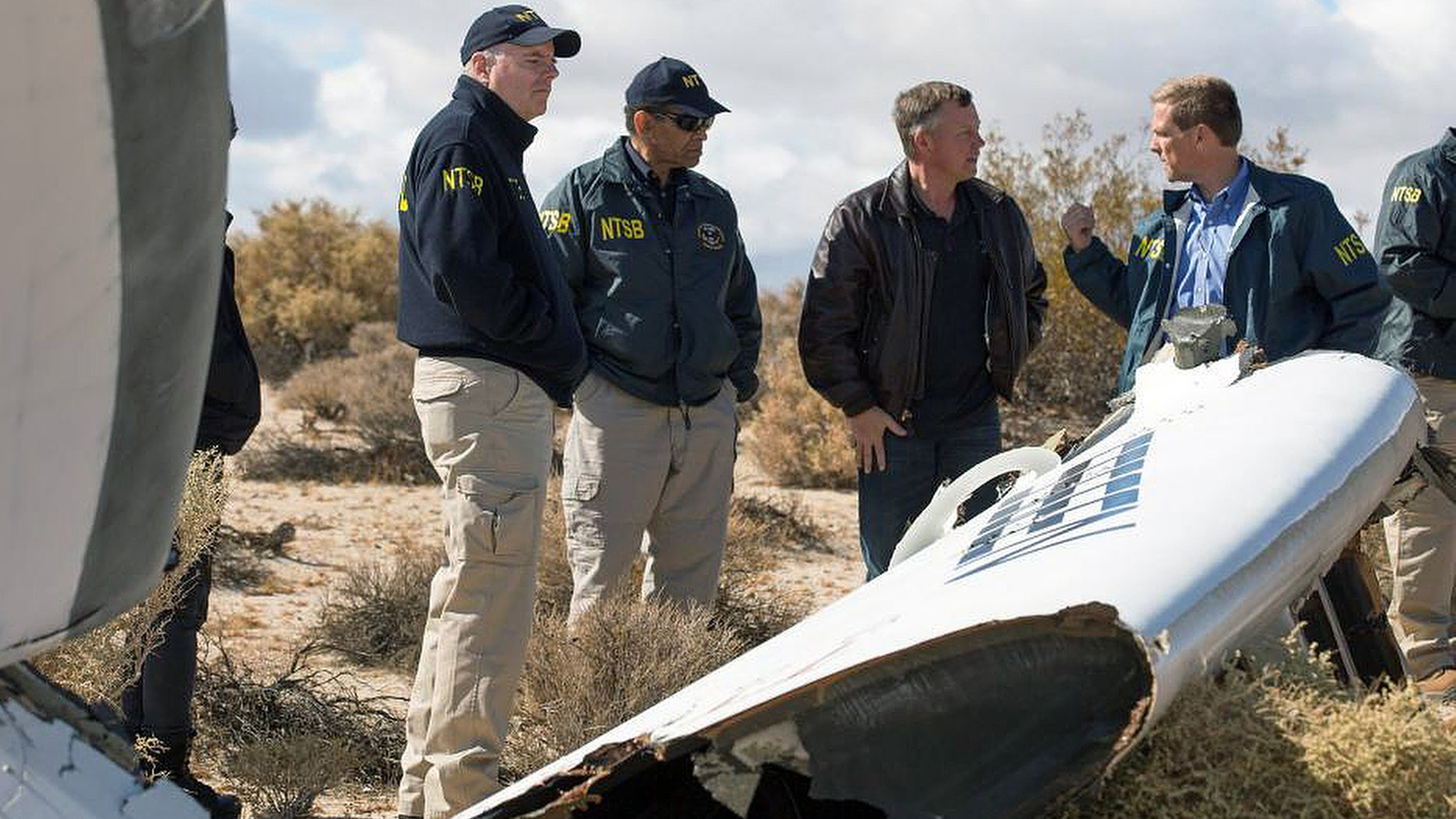 "In this Nov. 1, 2014, photo provided by the National Transportation Safety Board, Virgin Galactic pilot Todd Ericson, right, talks with NTSB Acting Chairman Christopher A. Hart, second from left, at the SpaceShipTwo accident site with investigators in Mojave, Calif. The cause of Friday's crash of Virgin Galactic's SpaceShipTwo has not been determined, but investigators found the ""feathering"" system, which rotates the tail to create drag, was activated before the craft reached the appropriate speed, National Transportation Safety Board Acting Chairman Christopher Hart said. (AP Photo/NTSB)"