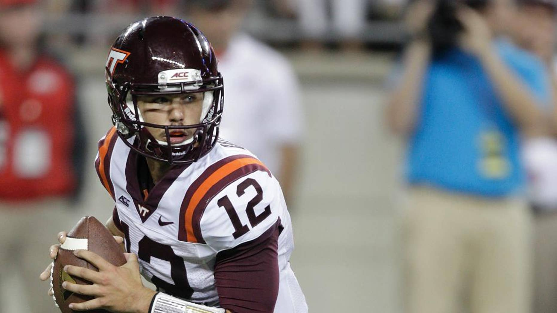 FILE- In this Sept. 6, 2014, file photo, Virginia Tech quarterback Michael Brewer rolls out against Ohio State during an NCAA college football game in Columbus, Ohio. Virginia Tech's loss to East Carolina made the high of winning the previous week at Ohio State a distant memory, Brewer said, and brought back into focus the Hokies' goal of playing well when they begin Atlantic Coast Conference play on Saturday against Georgia Tech. (AP Photo/Jay LaPrete, File)