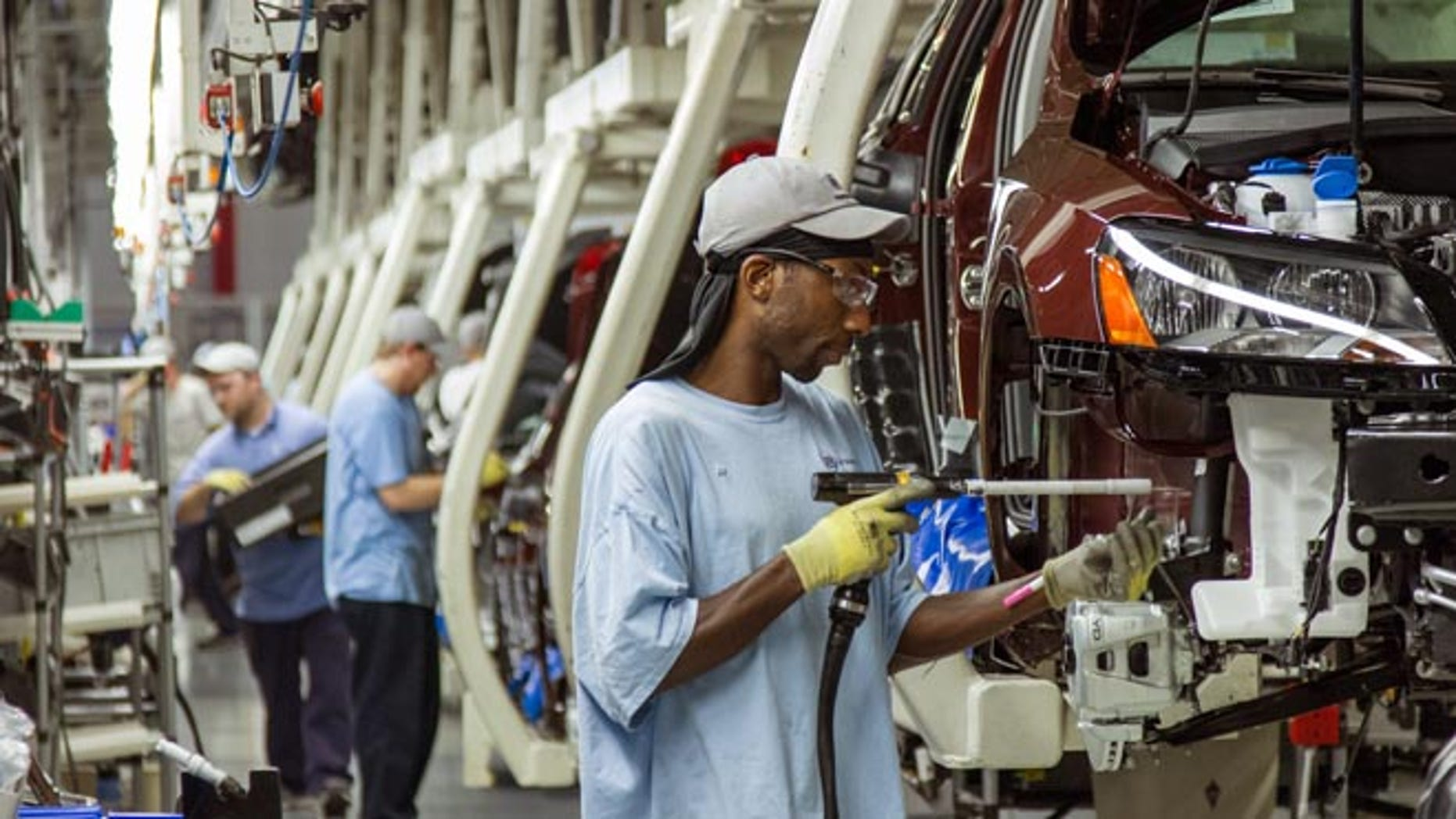 In this June 12, 2013 file photo, workers assemble Volkswagen Passat sedans at the German automaker's plant in Chattanooga, Tenn.